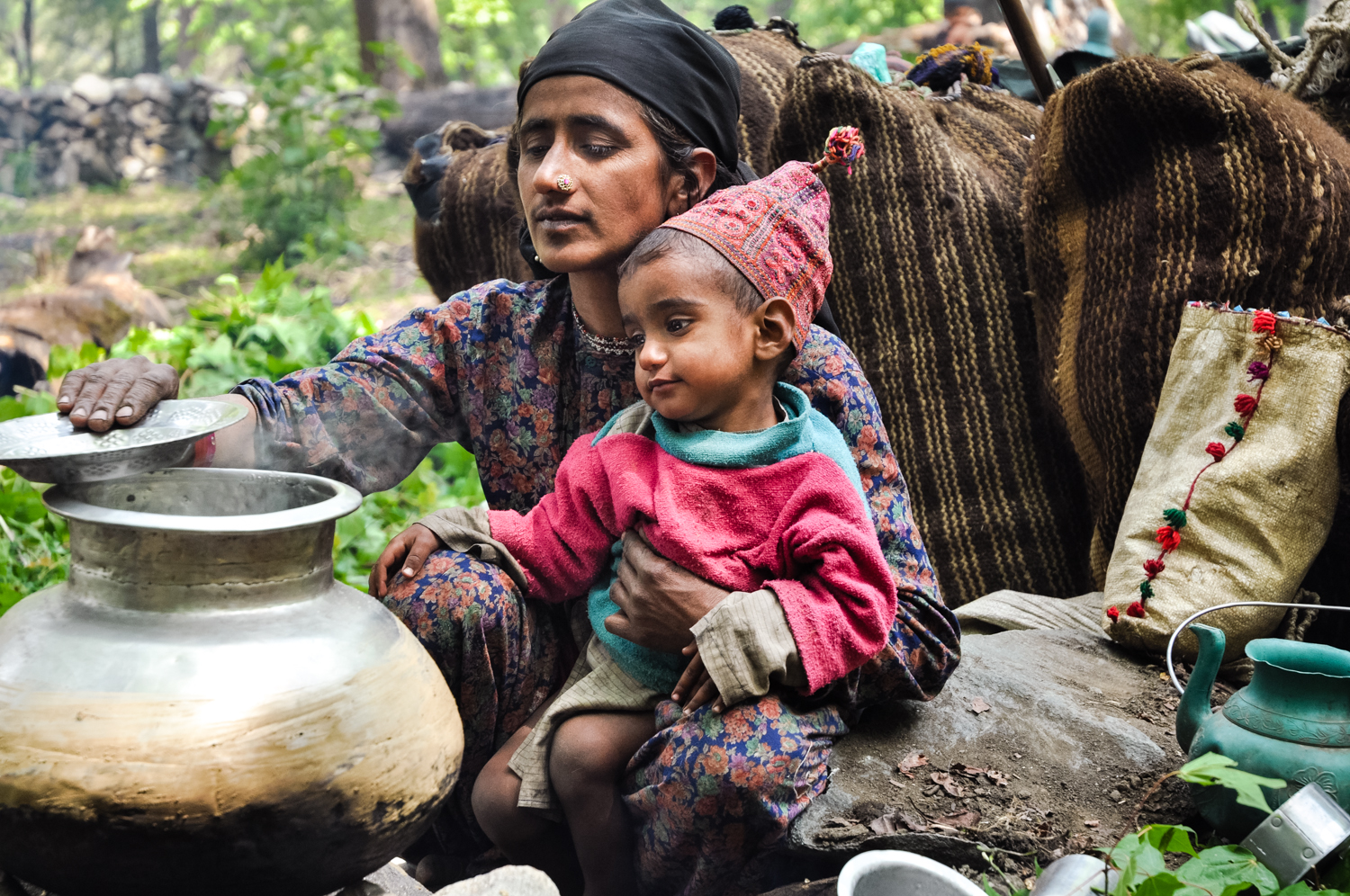 Jamila, with her 2-year-old son, Yasin, makes lunch along the trail.
