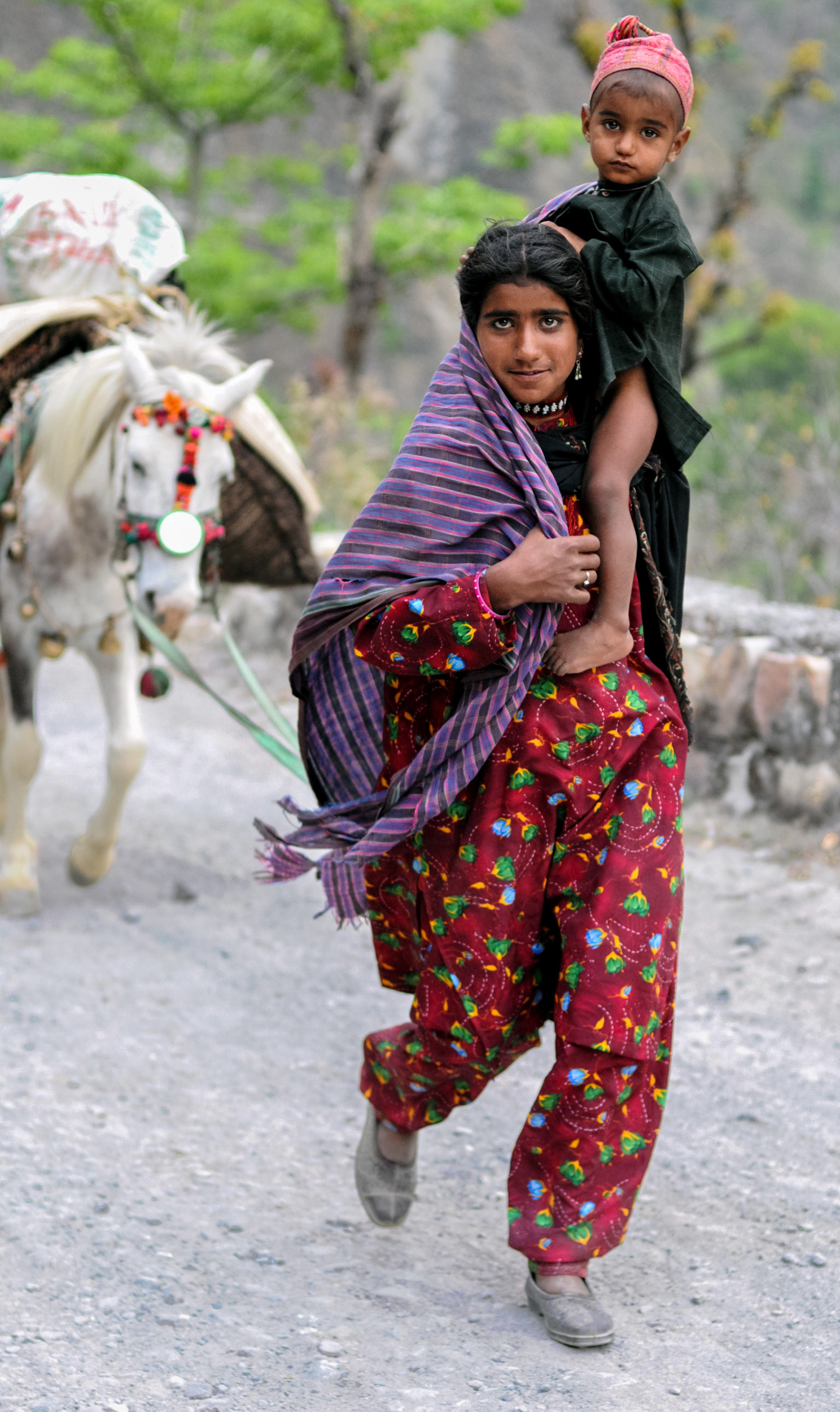 Goku leads a pack horse while carrying her brother, Yasin, as the family moves up the Yamuna Valley.