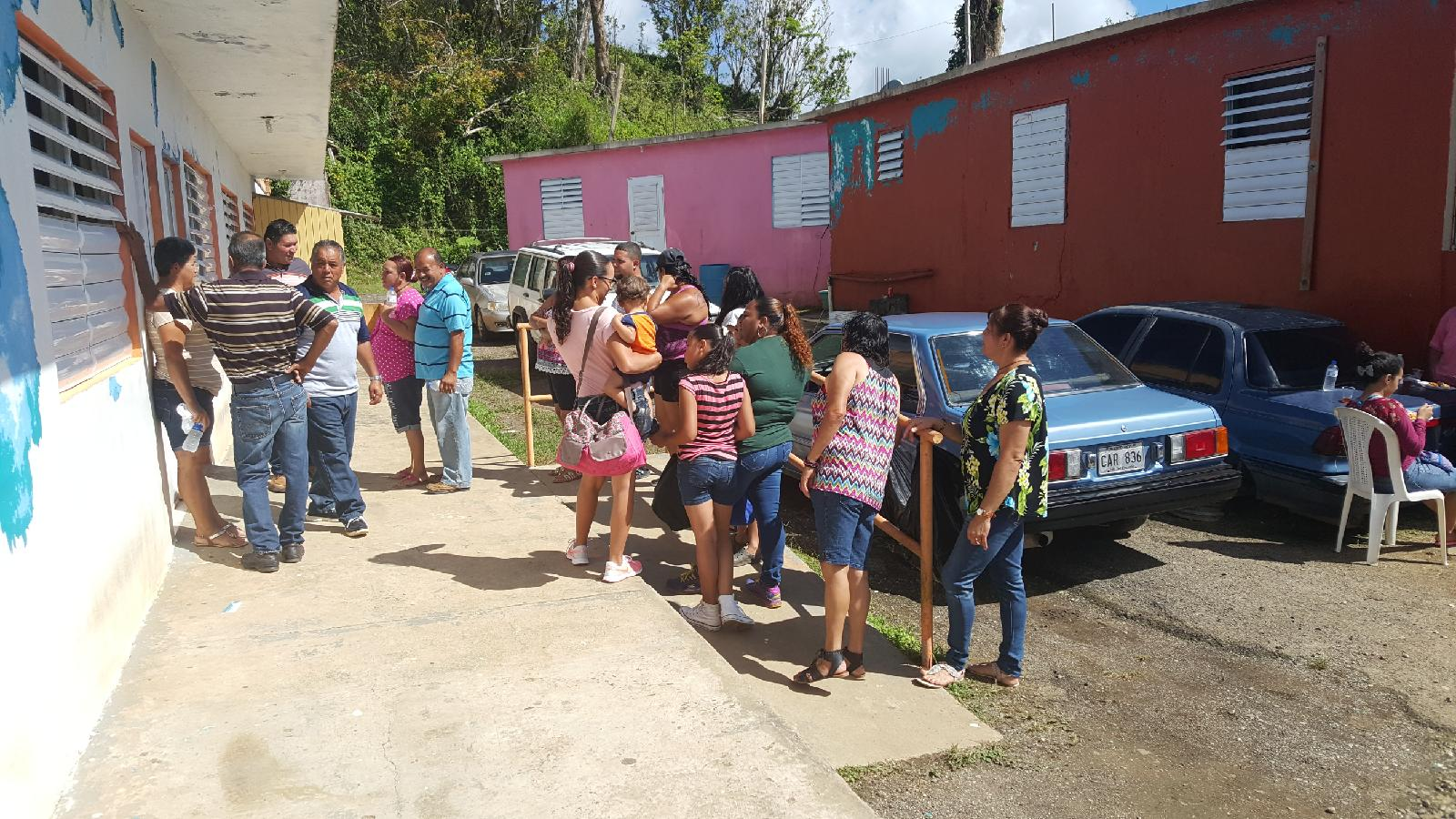 Patrons waiting in line in Yauco, PR for medical services and basic supplies such as lanterns, blankets, and formula.