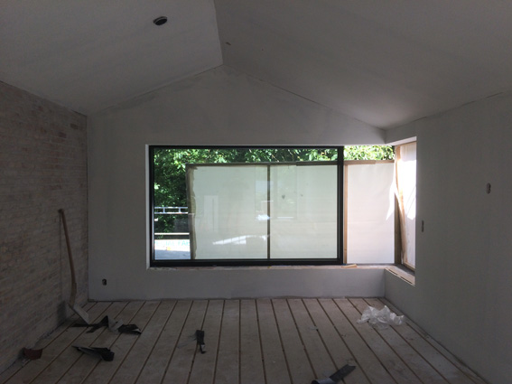 Gipsvægge bliver etableret og store vinduer monteres for at skabe flot lysindfald.