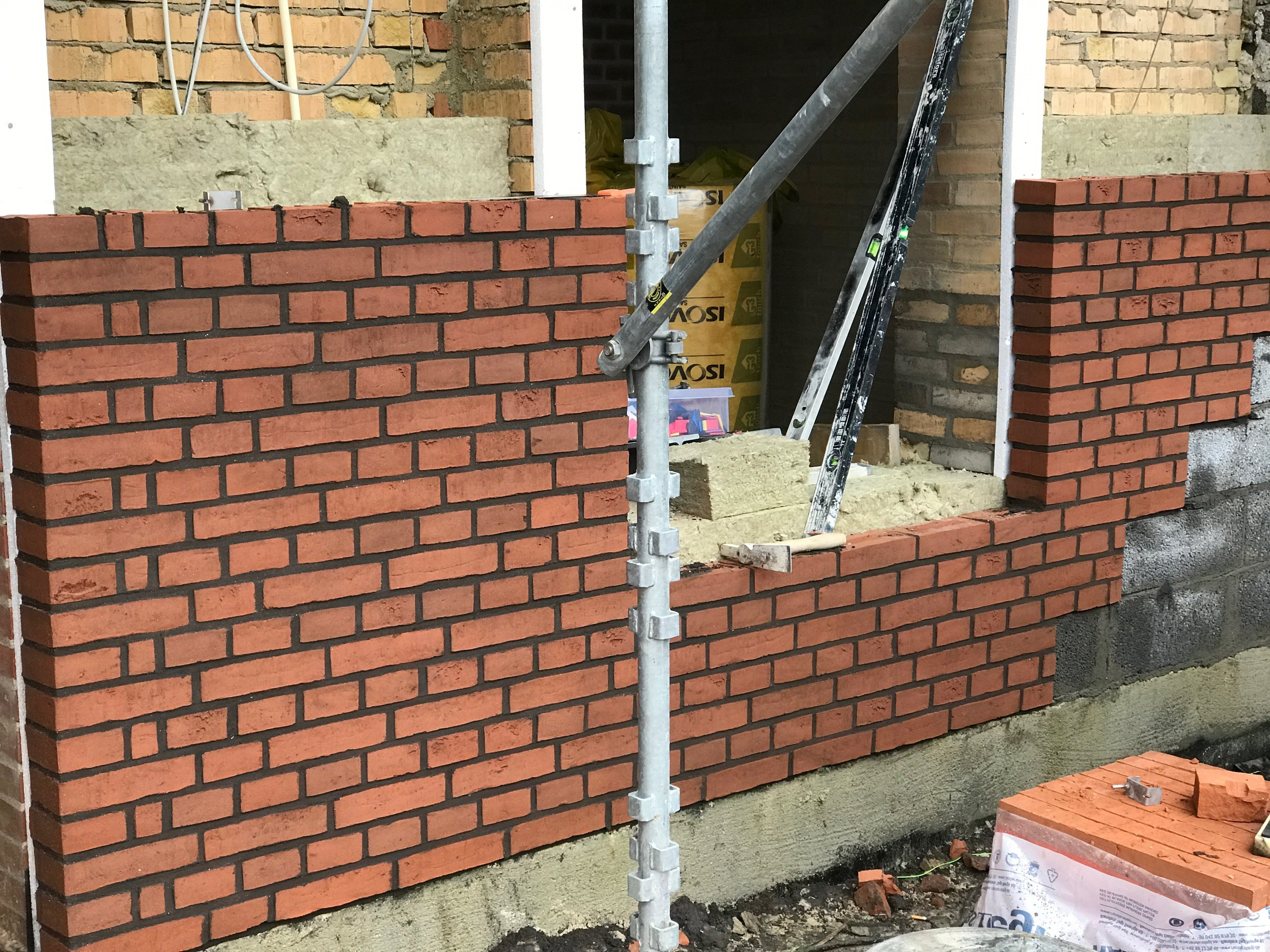 Skalmuring af facademuren i røde mursten.