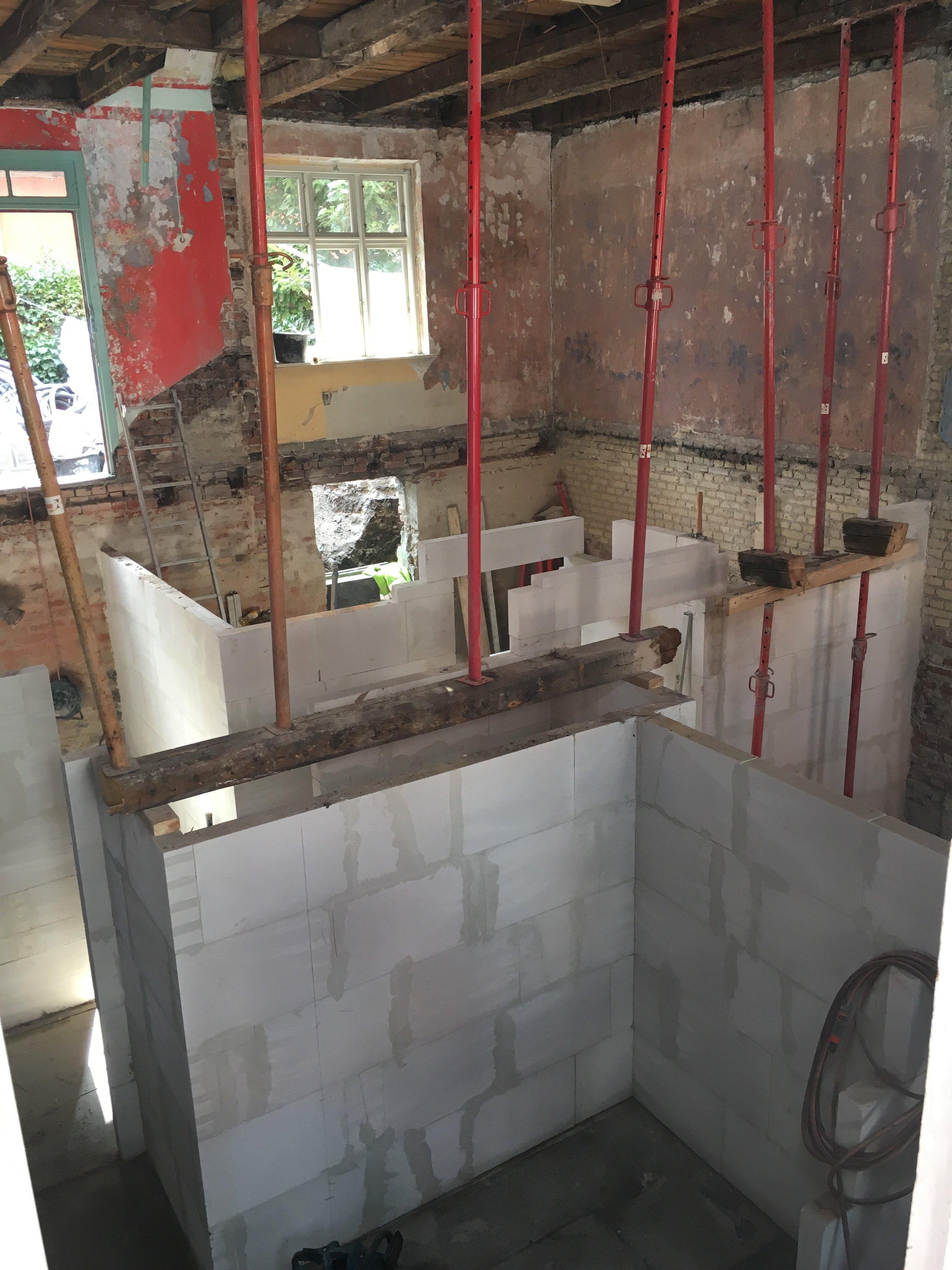 Bærende vægge og dæk imellem etager brydes ned og ny rumfordeling bygges op.