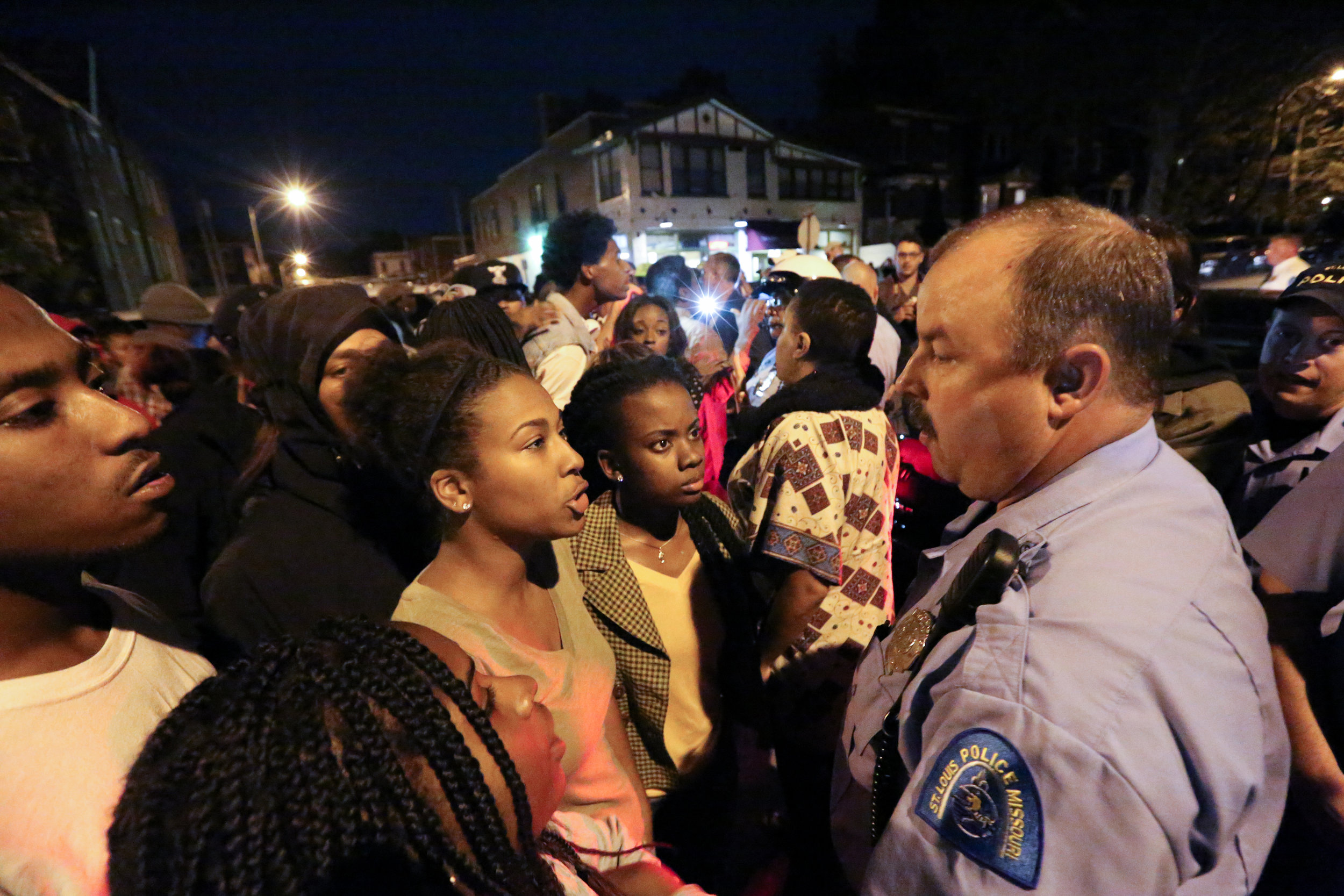 Alexis (left) and Brittany confront a police officer as the vigil for Vonderrit Myers Jr. is interrupted with an order to disperse.