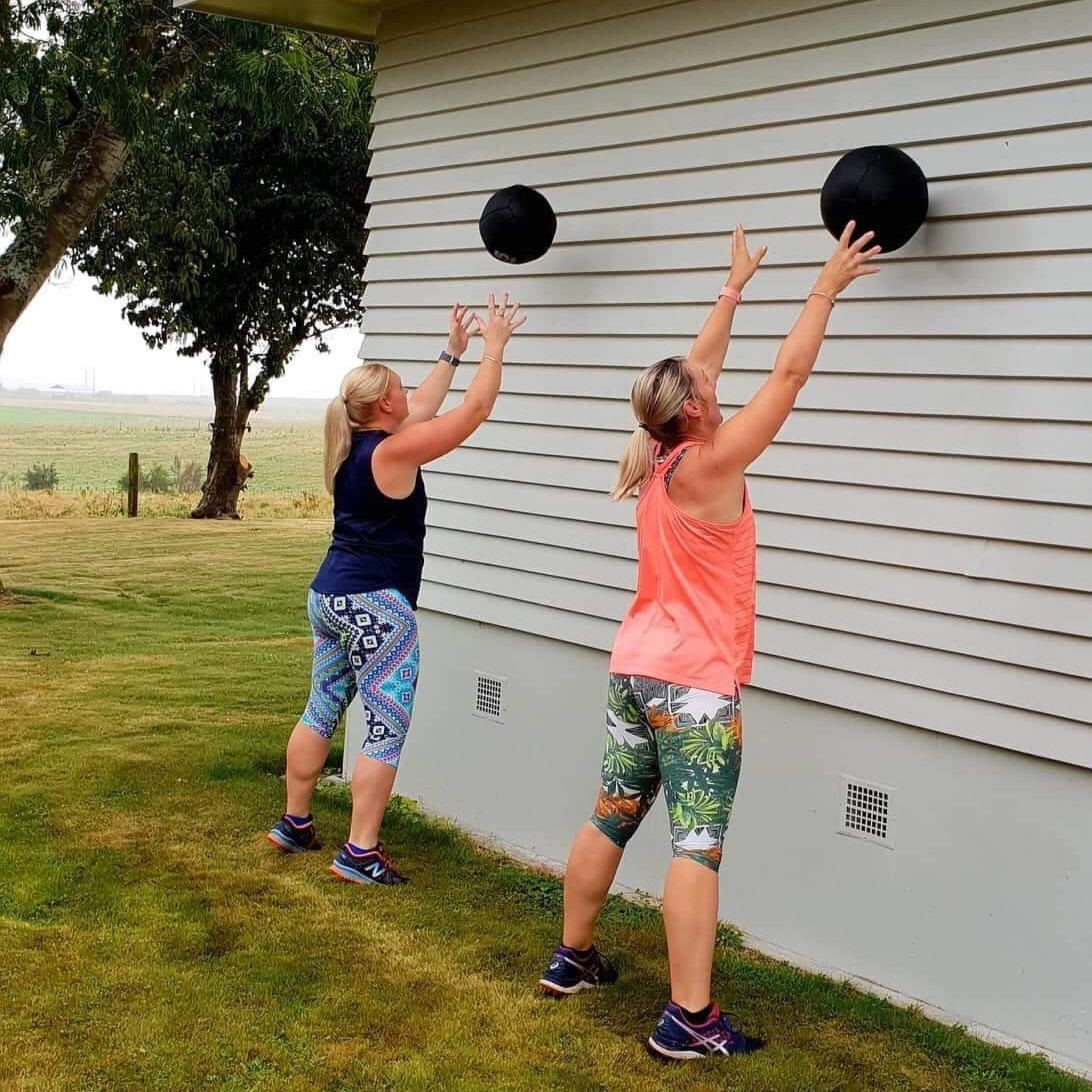 ladies throwing balls up against wall.jpg