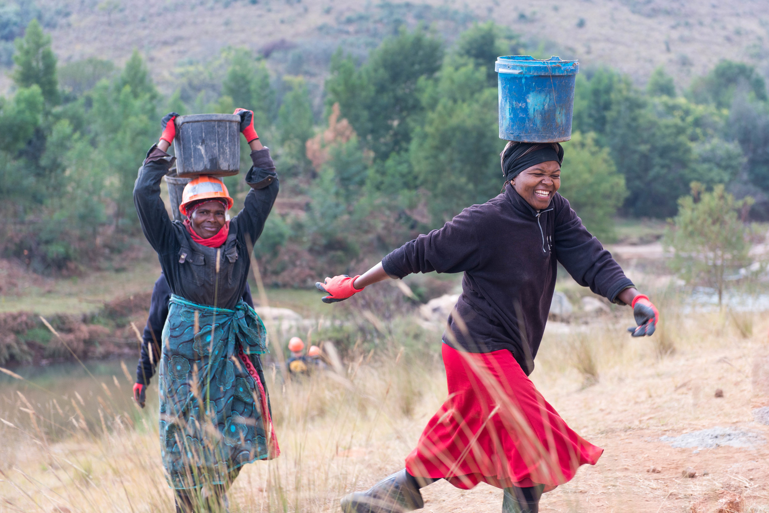 Carrying sand and water was a daily task on the bridge site. Edlangeni, Swaziland
