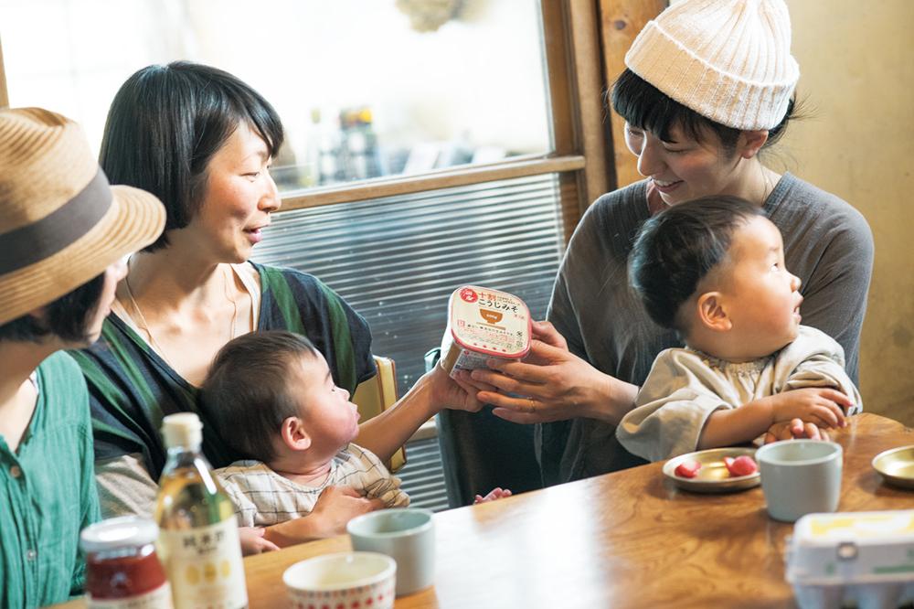 佐藤さん(左)は8カ月の穂尚(ほだか)くんのお母さん。子育て真っ最中の現在は、野菜や調味料を中心にそろえている。愛用している国産十割りこうじみそを持参