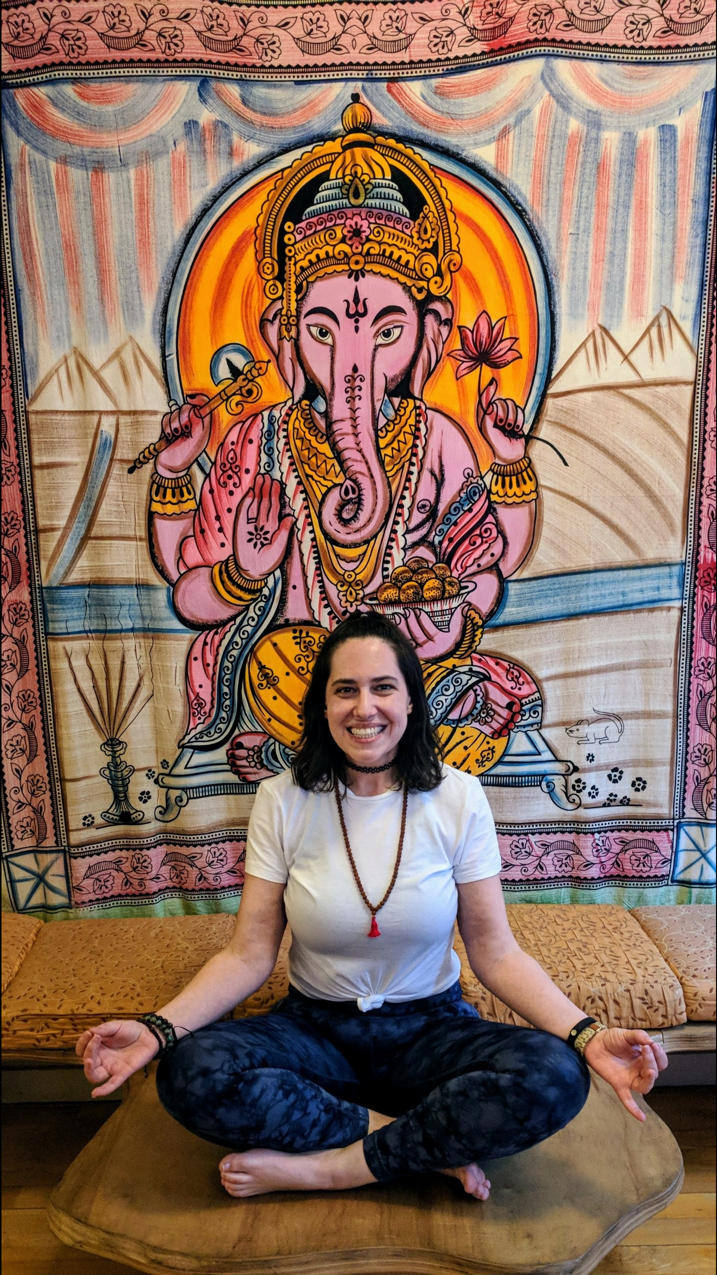 Jaime Ormont in the easy yoga pose wearing mala beads and a white t-shirt about to meditate in front of a Ganesh tapestry.