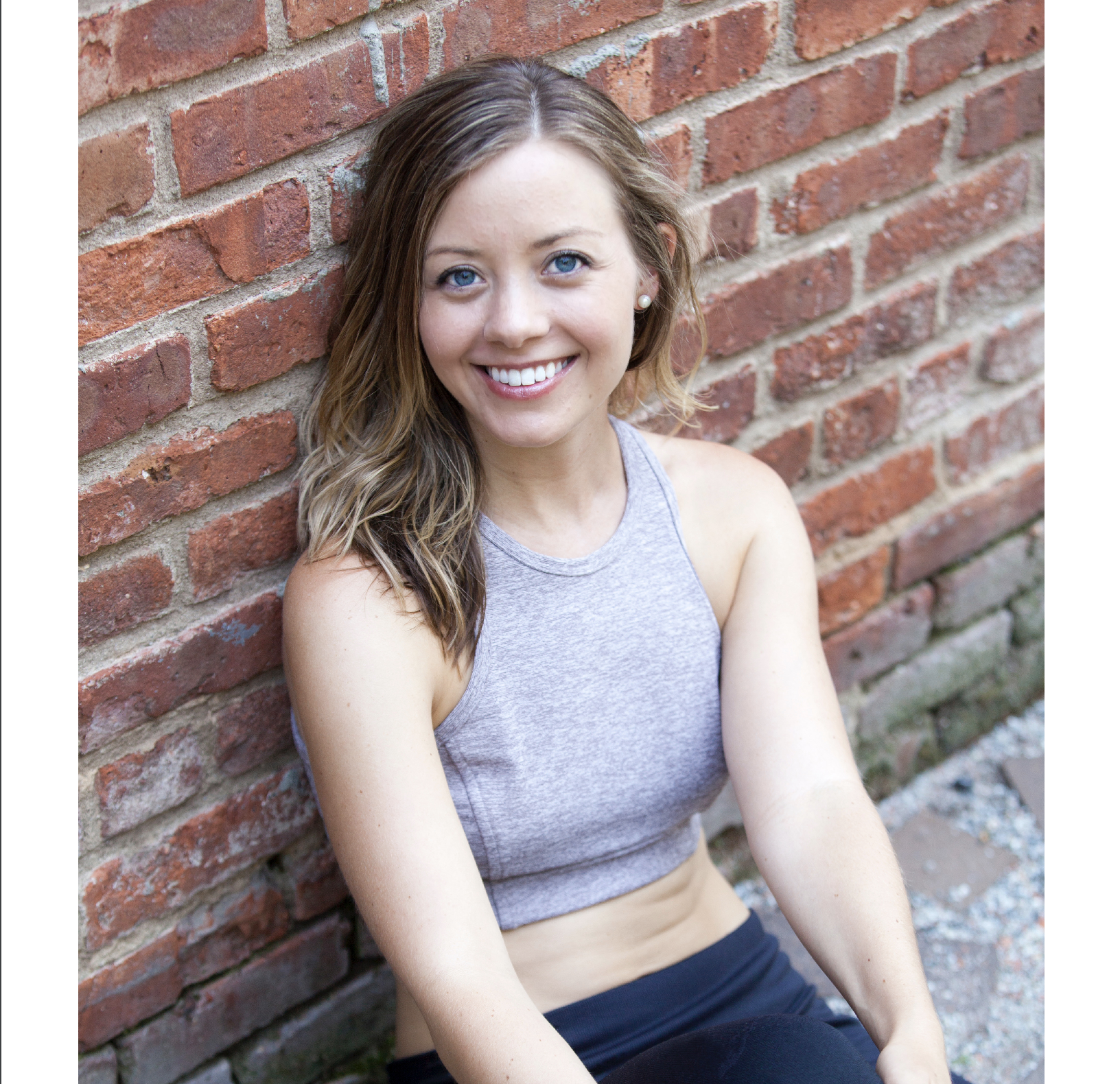 Natalie Tyson-Multhaup in gray crop top leaning against brick wall smiling