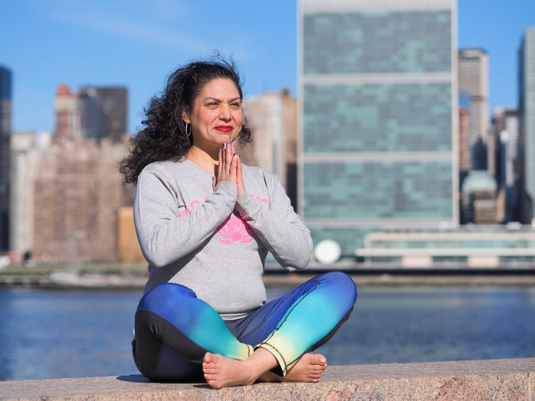 Yoga teacher Jen SanMiguel sitting in the easy yoga pose with hands in prayer and East River and New York City in background