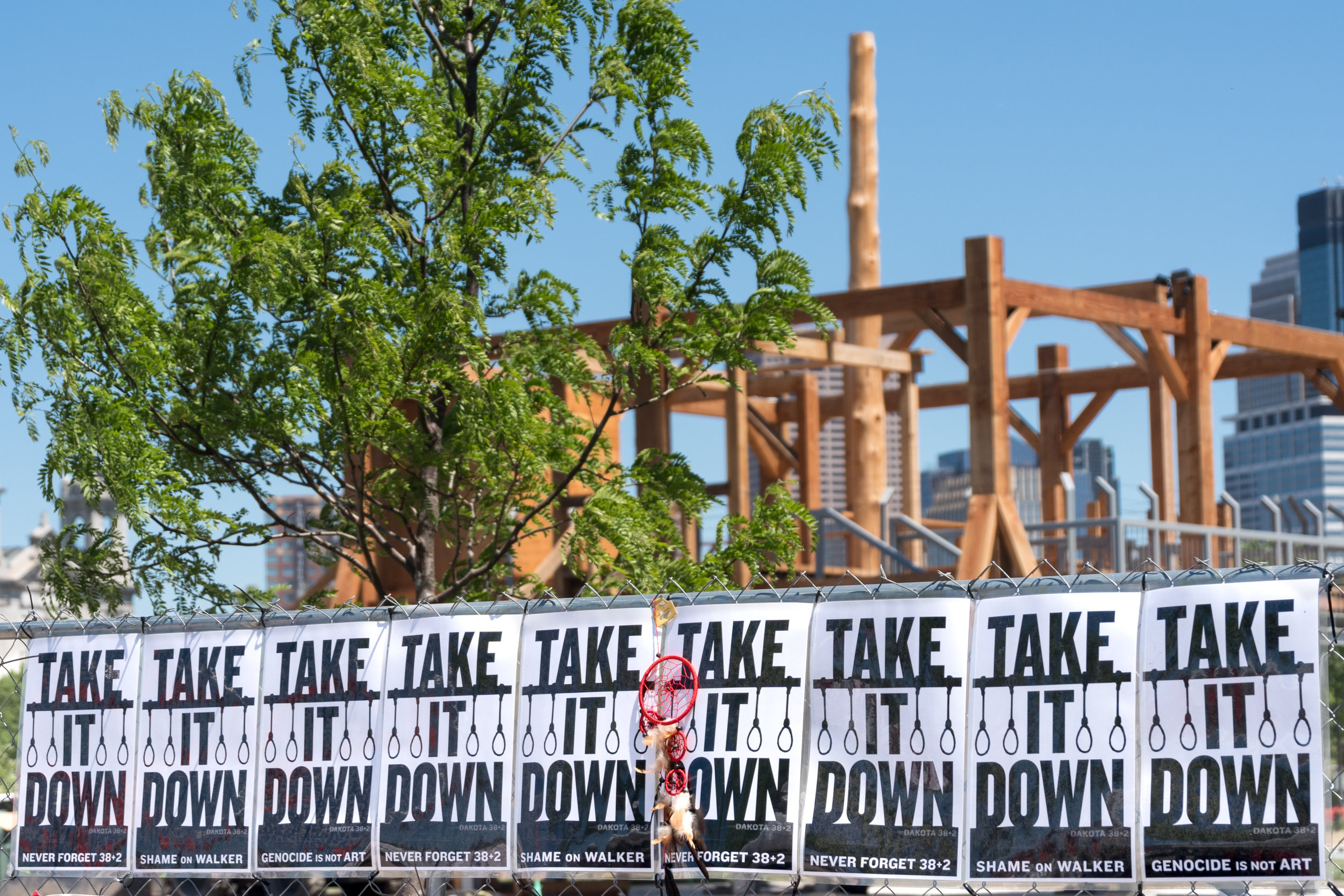 """The """"Scaffold"""" sculpture by Sam Durant with """"Take It Down"""" protest signs on the perimeter fence surrounding the Minneapolis Sculpture Garden"""