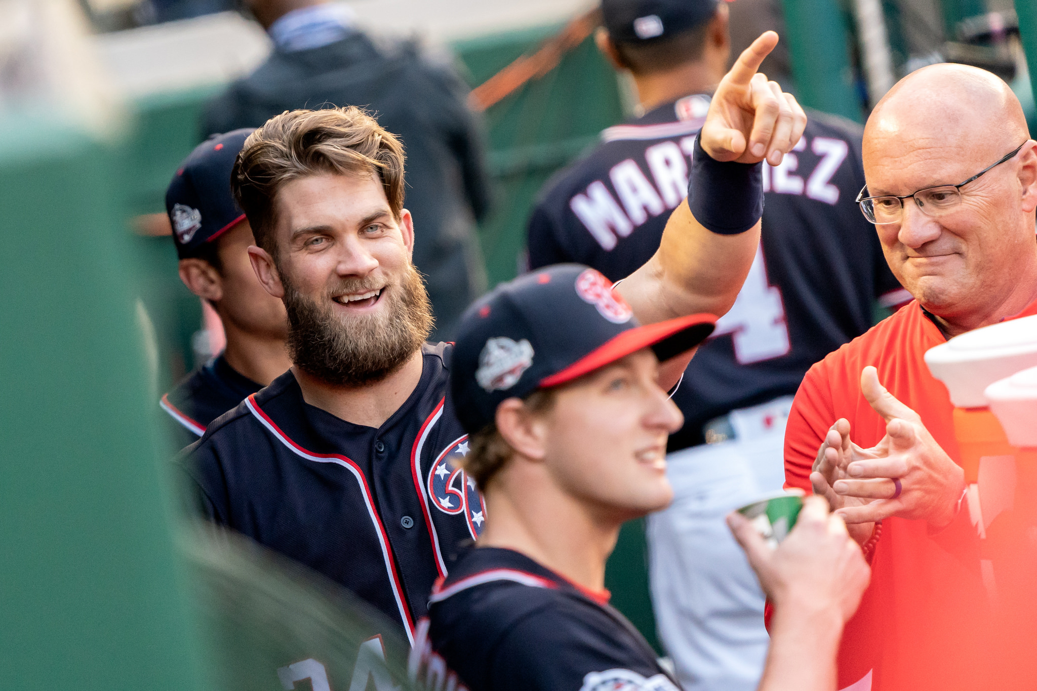 Bryce Harper points to the scoreboard from the dugout when Andrew Stevenson is announced at the beginning of the game, Washington Nationals Park