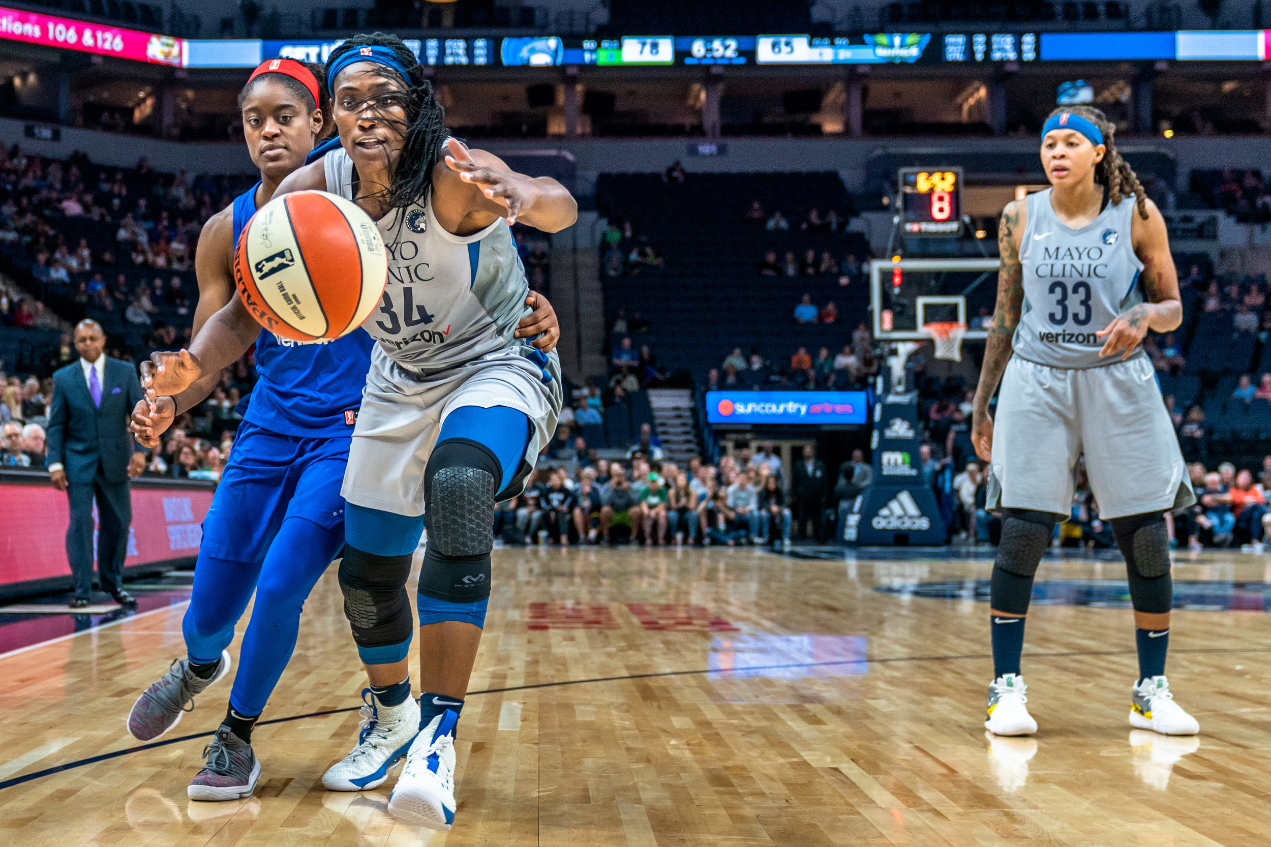 Sylvia Fowles saves a ball from going out of bounds as she's guarded by Kaela Davis in the Minnesota Lynx vs Dallas Wings game at Target Center.