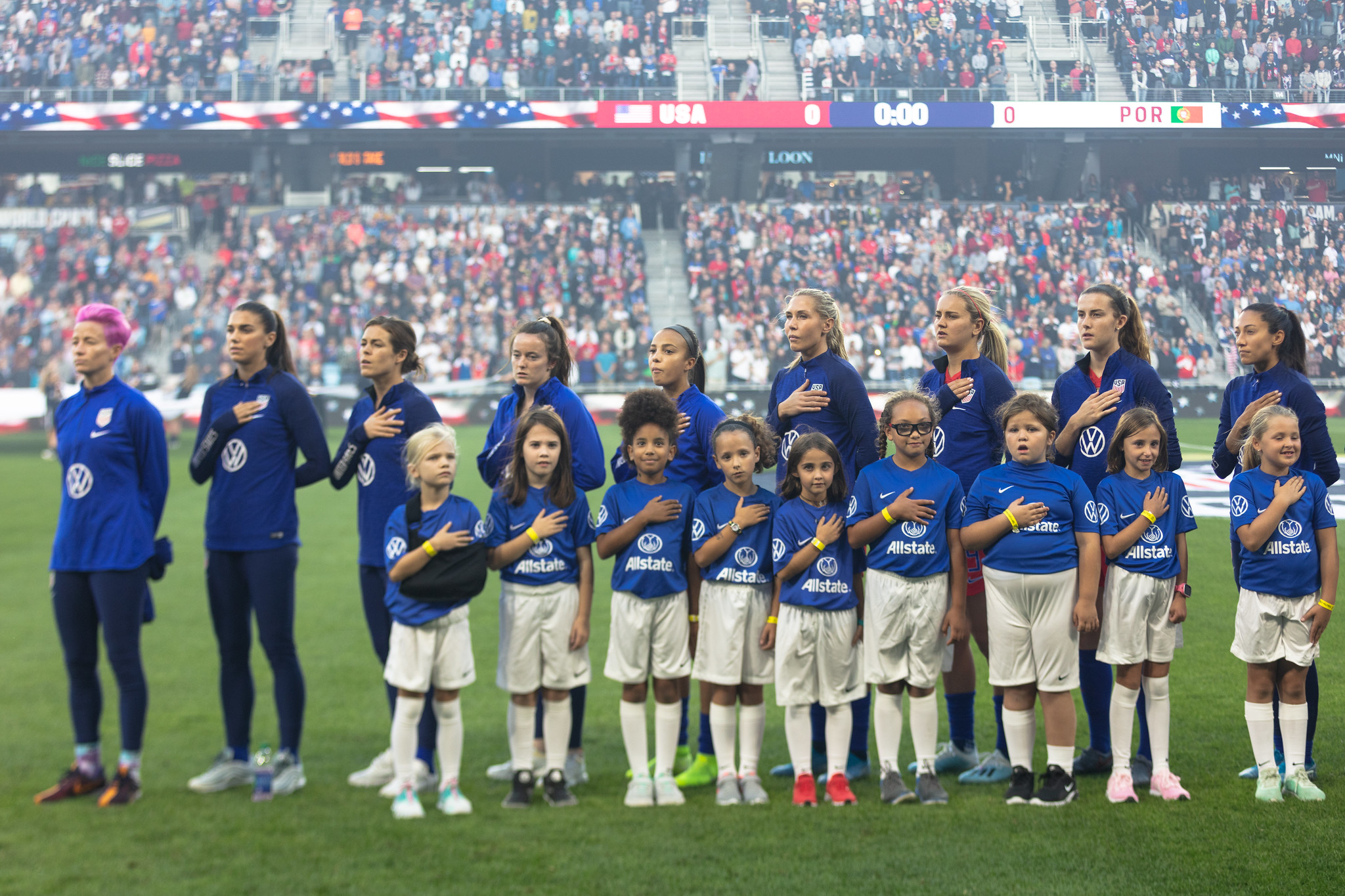 Team USA stands for the National Anthem before the match with young soccer players