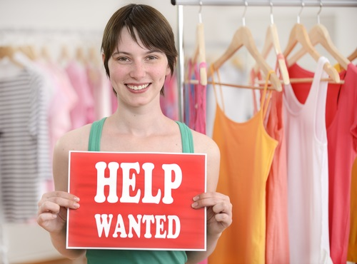 retail-store-owner-holding-help-wanted-sign.jpg
