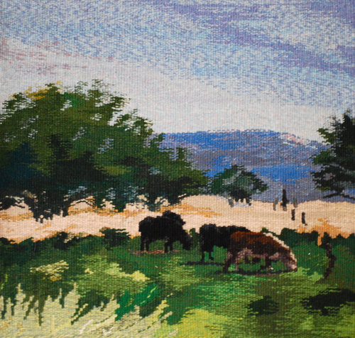 """MAY  This is a familiar scene where I live:the cows enjoying new grass, the greening of the trees, and the mountains, still with bits of snow, in the background. This tapestry is 18""""x18"""", is woven in wool and mounted on a frame."""
