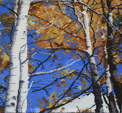 """OCTOBER  The Colorado mountains turn gold in October, with the Aspen trees showing off their beauty. We are often under the trees, cutting deadwood for our fireplace, and marveling at the bright blue autumn sky. This tapestry is 18""""x18"""" and is woven in wool."""