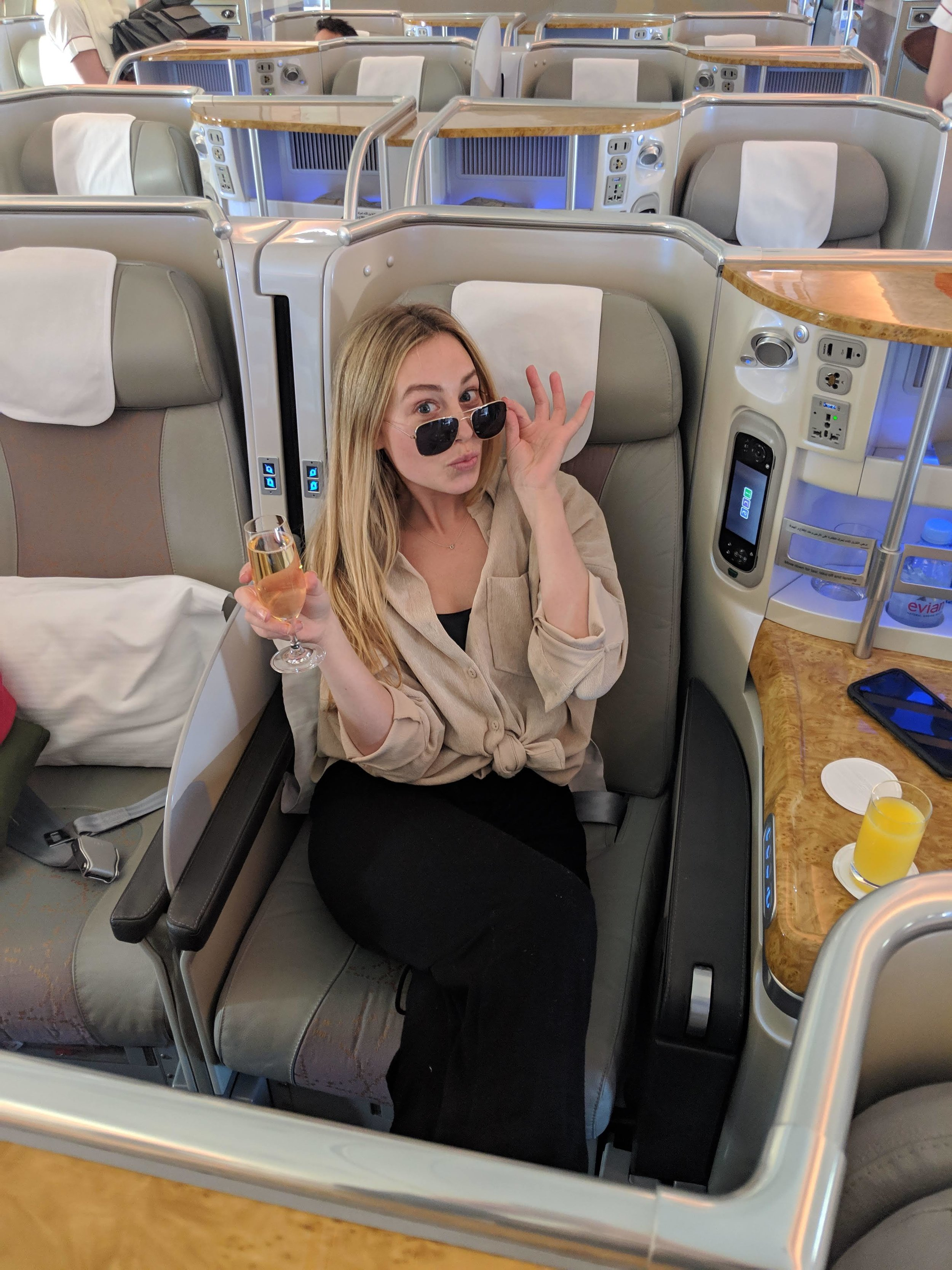 woman in Emirates business class with champagne