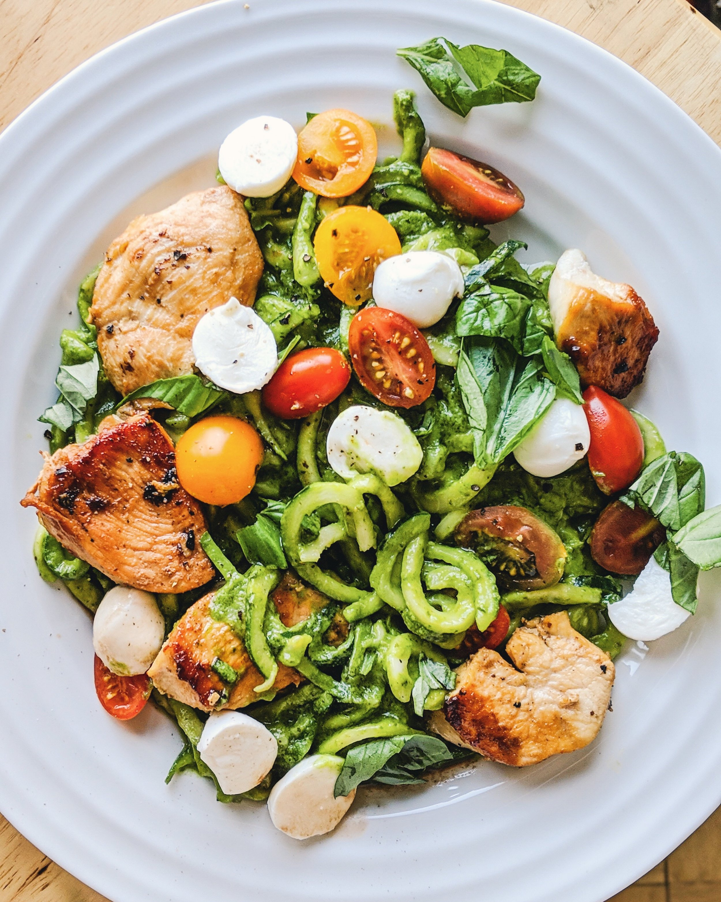 Chicken Caprese Zoodles with Spinach Avocado Pesto - A light and nutritious way to eat your favorite caprese salad. Sweet cherry tomatoes and ciliegine mozzarella with fresh basil, on top of a bed of creamy avocado pesto zucchini noodles with seared garlic chicken.