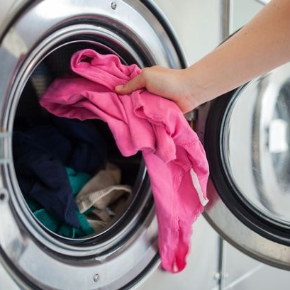 Woman-putting-shirt-into-washing-machine.jpg