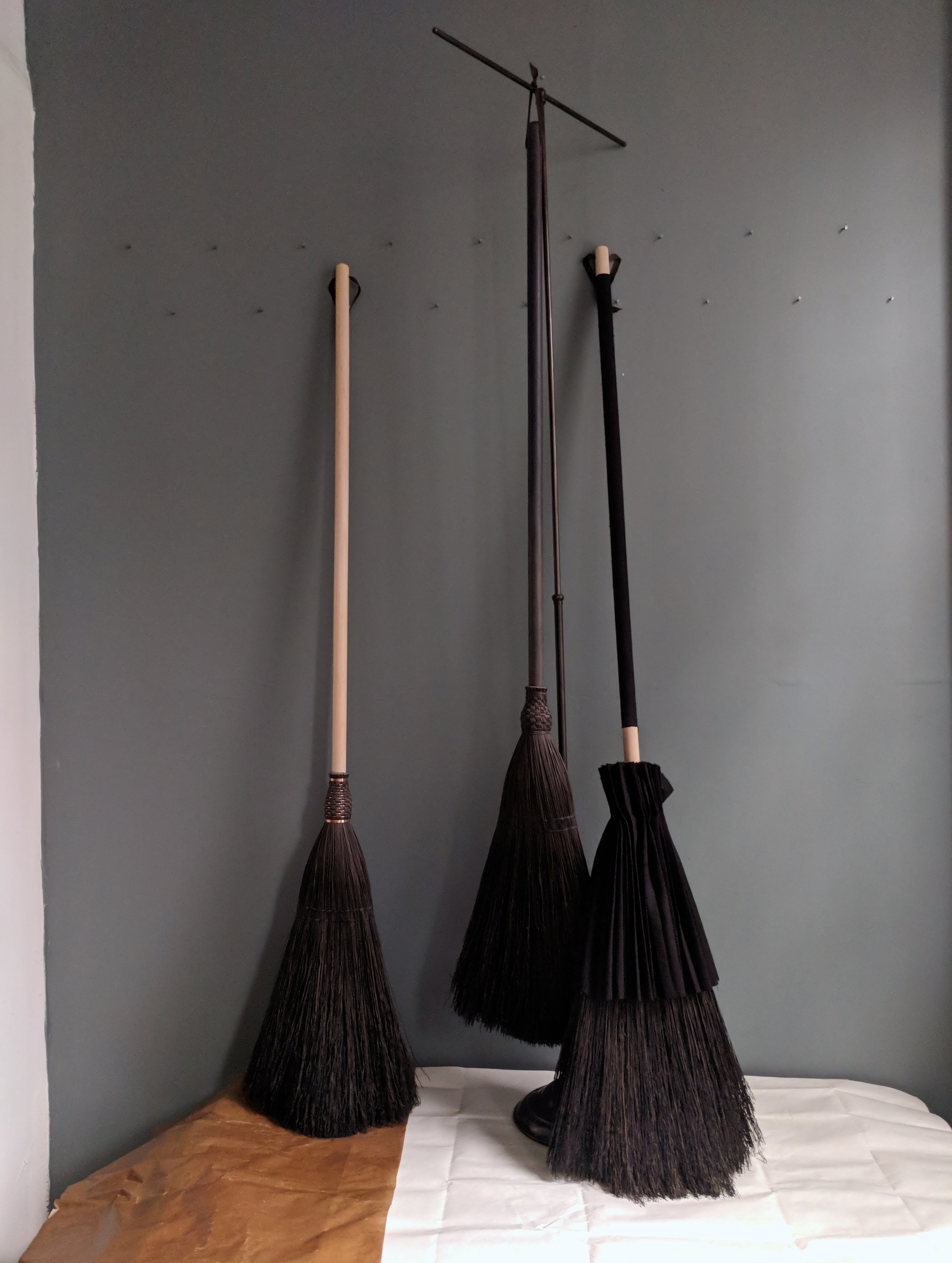 trio of black brooms with stand.jpg
