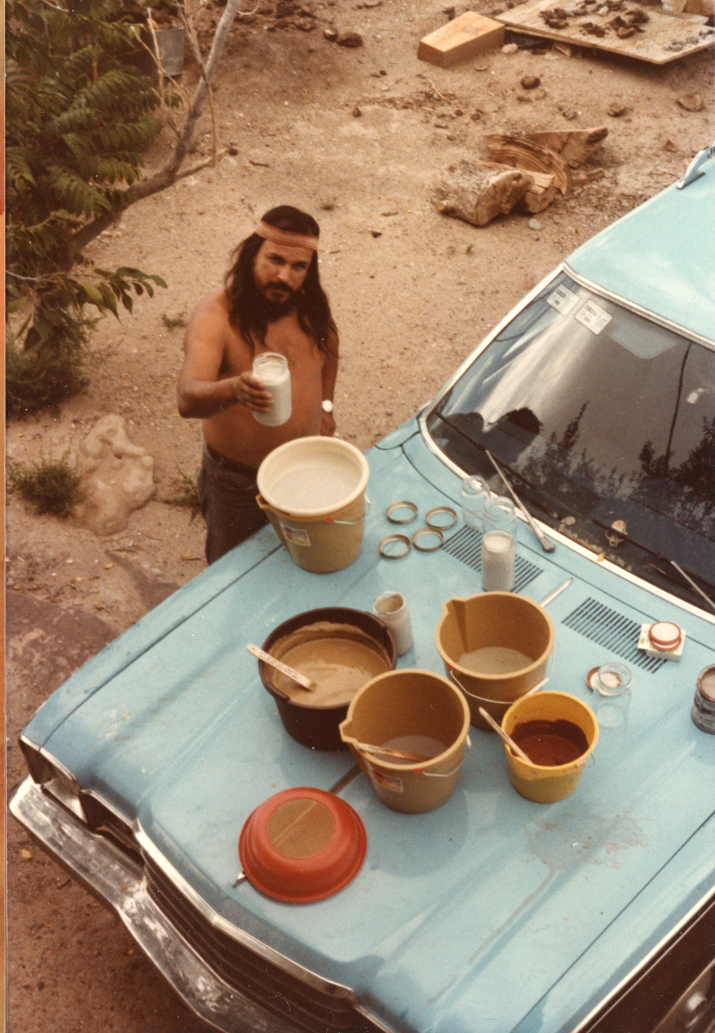 Anong's dad processes earth pigments on the hood of the family stationwagon, circa 1970s.  Photo courtesy of Anong Migwans Beam.