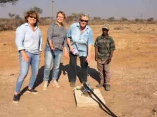 CSNS Board Members Diane Mawson and Betty Owen with CSN Board member Helge Mercker and Gardener/Handyman, Zuma pointing to the borehole or well funded by CSNS donors.