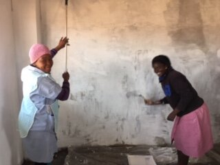 """Soup kitchen volunteers, Amanda and Meena busy painting one of several rooms in the """"Moeder Huis"""". The progress of the building brings great hope and inspiration to the volunteers and to many in the community."""