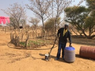 Moses the Security Guard with a hippo roller used to transport water to his home located outside the fenced area.