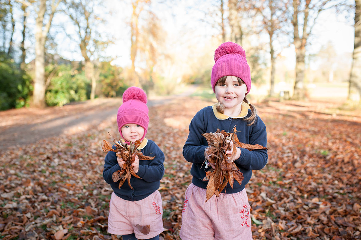 Sisters in Autumn throwing leaves (1).jpg
