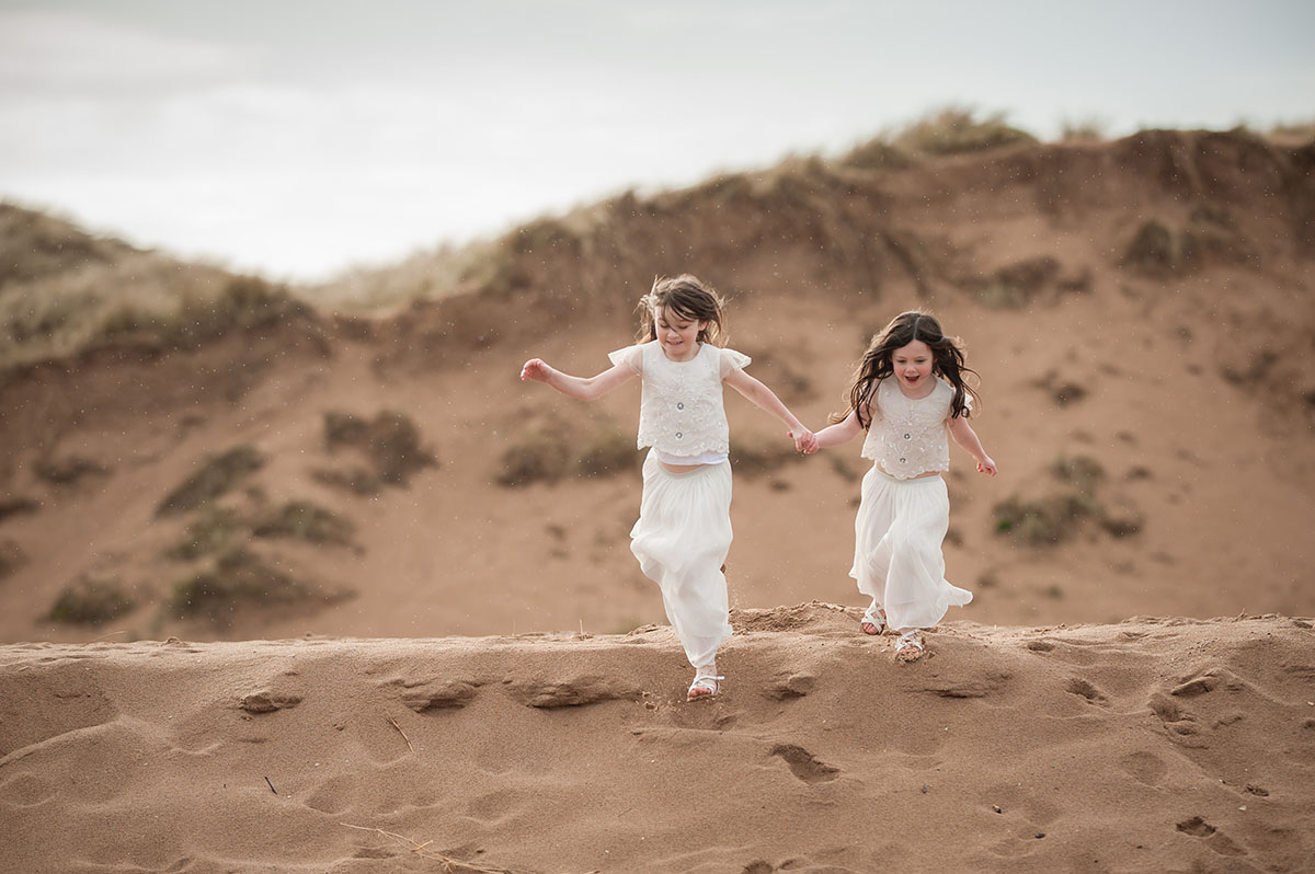 Sisters running down sand dunes on Angus beach.jpg
