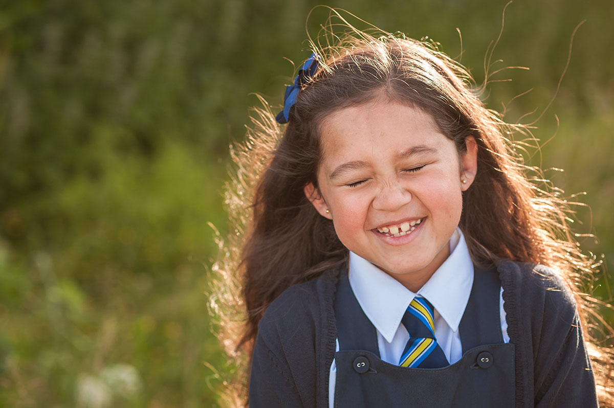 Little girl giggling in school uniform (1).jpg