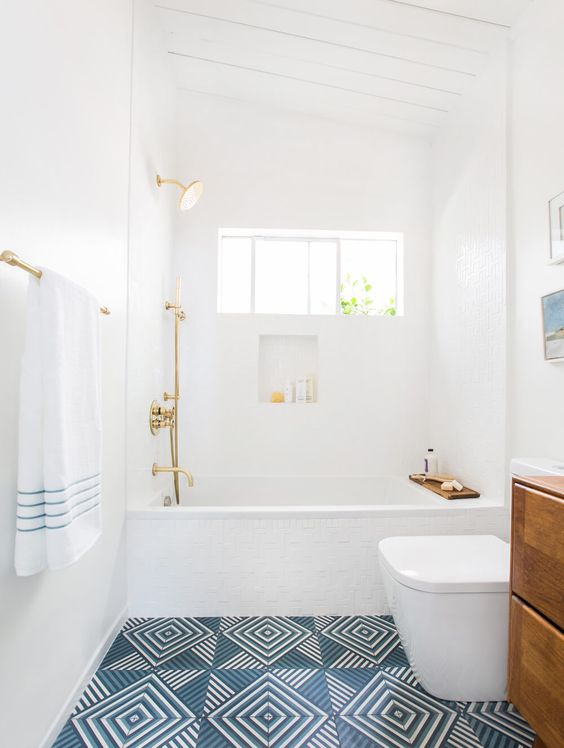 if you're adding a vibrant pattern to your space, be sure to keep the rest of your design clean and easy on the eye. coordinating fixture and wood finishes along with clean white walls, a white toilet and tub keeps this space perfectly balanced.