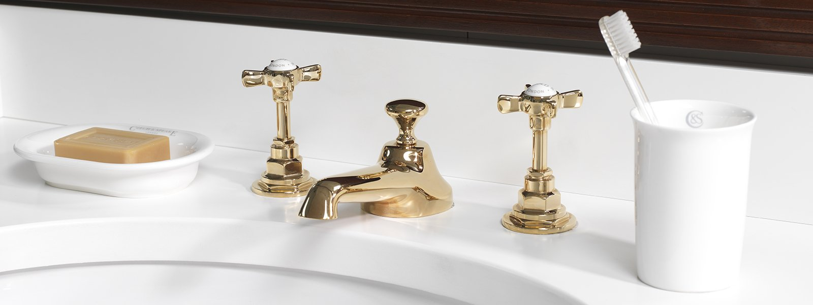 czech & speake deco widespread lav faucet with low spout and tall cross handles with porcelain inset in unlacquered brass - the ultimate guide to luxury plumbing by the delight of design