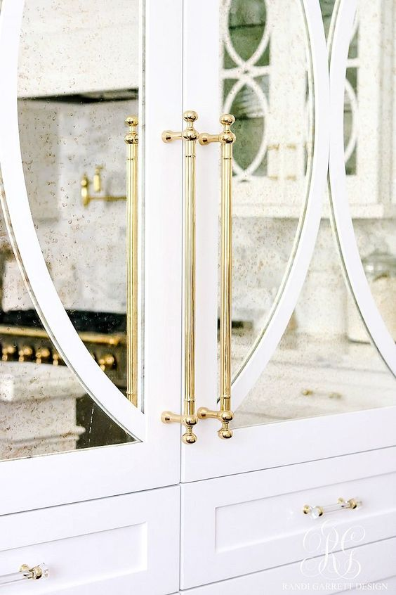 white cabinets with antiqued mirror and decorative mullion inserts with unlacquered brass hardware