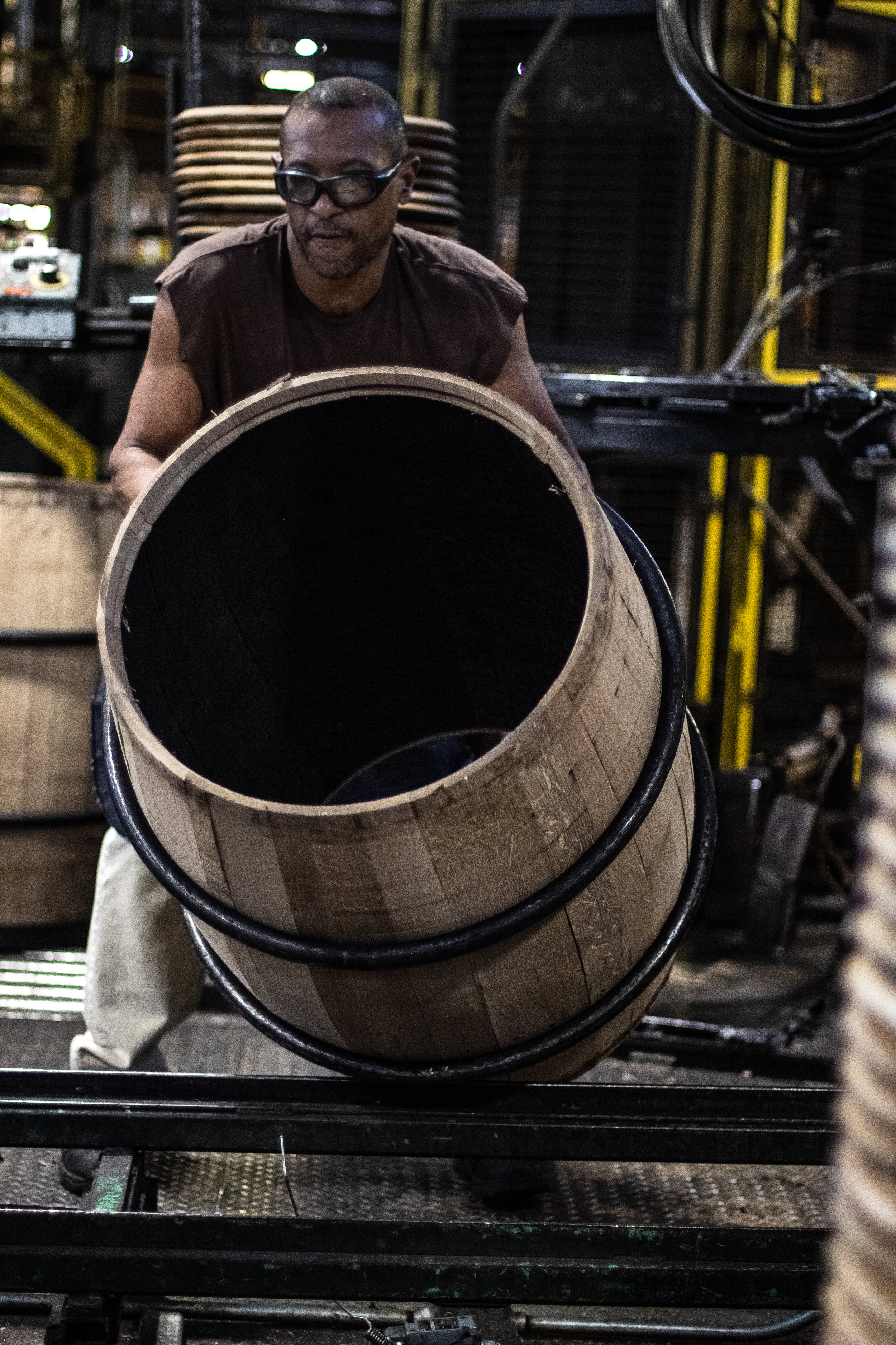 A worker, rolling a recently charred barrel to its next station.