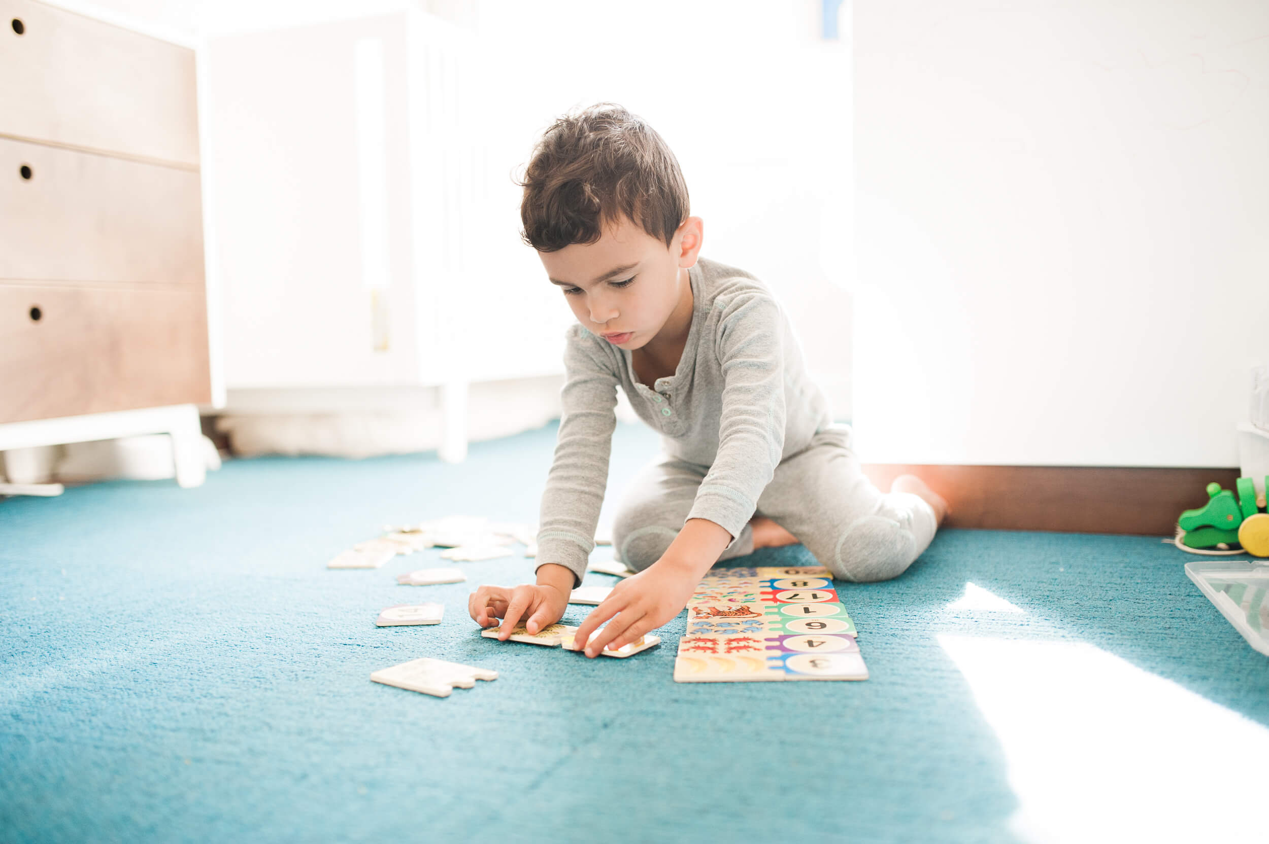 Child building a puzzle at home Brooklyn lifestyle family photographer based in Litchfield County, CT at home in Cobble Hill neighborhood by Lindsey Victoria Photography