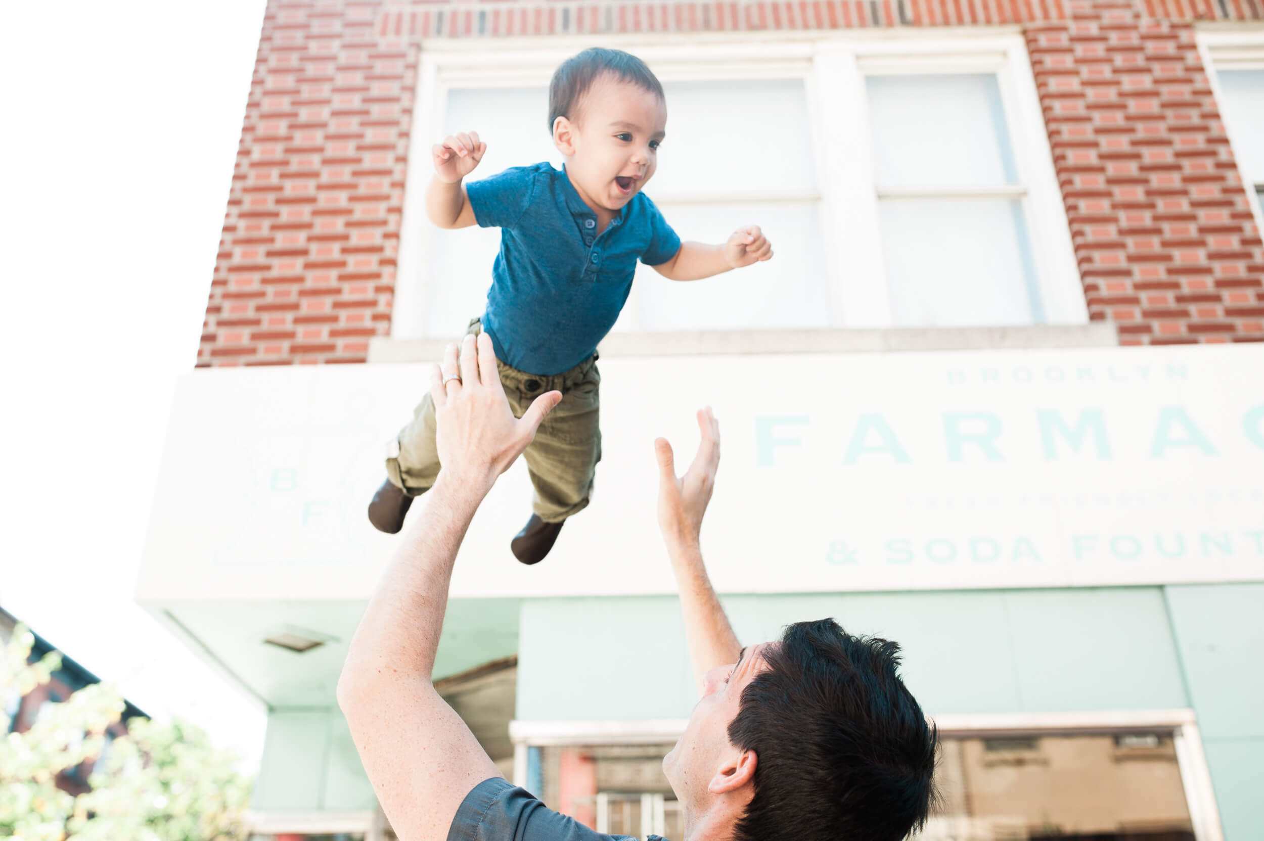 Father tossing baby in the air in Cobble Hill at Brooklyn Farmacy in Brooklyn New York family photography lifestyle session by Lindsey Victoria Photography