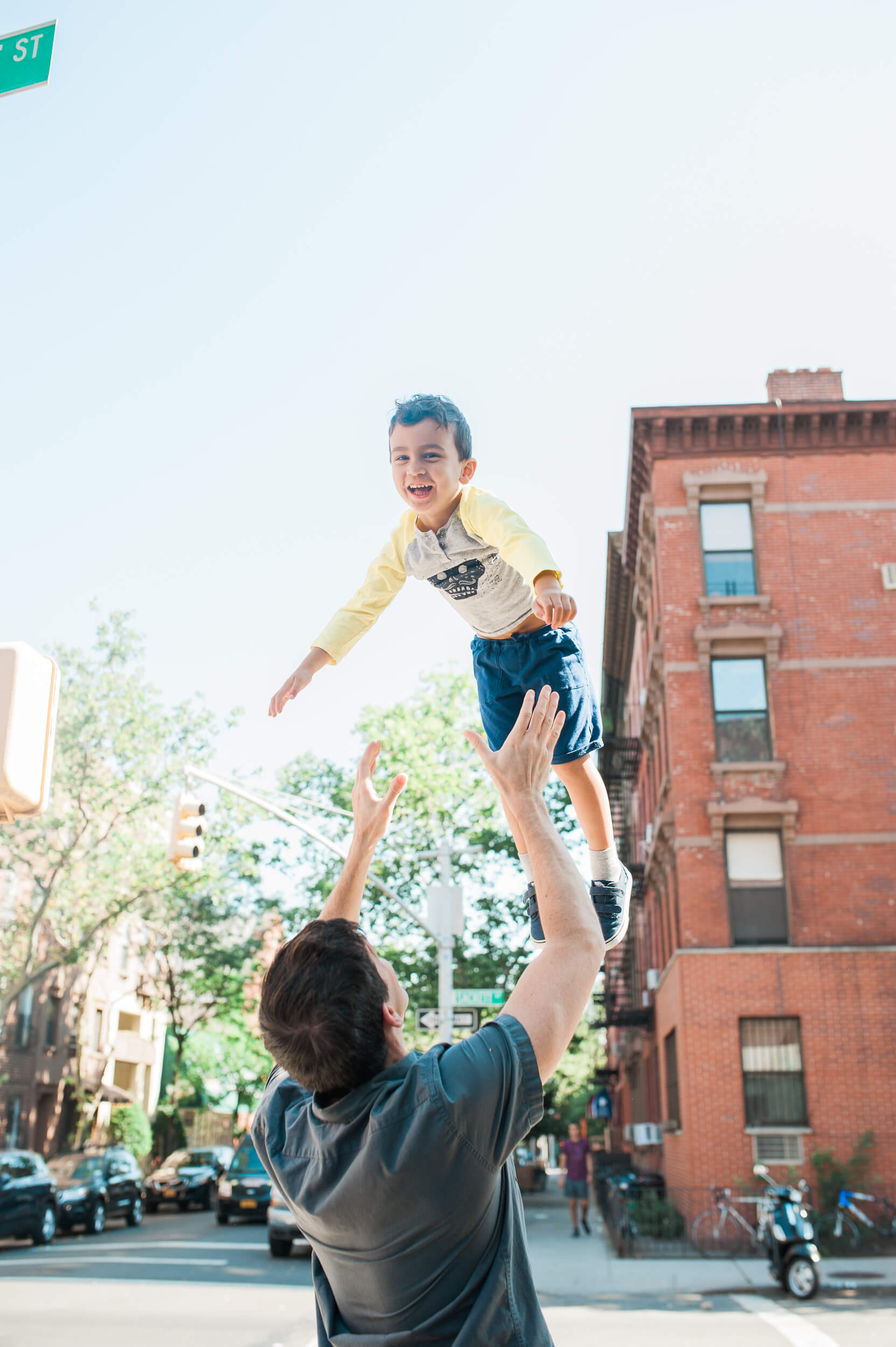 Father tossing son in the air in Cobble Hill Brooklyn New York family photographer lifestyle session in Cobble Hill by Lindsey Victoria Photography