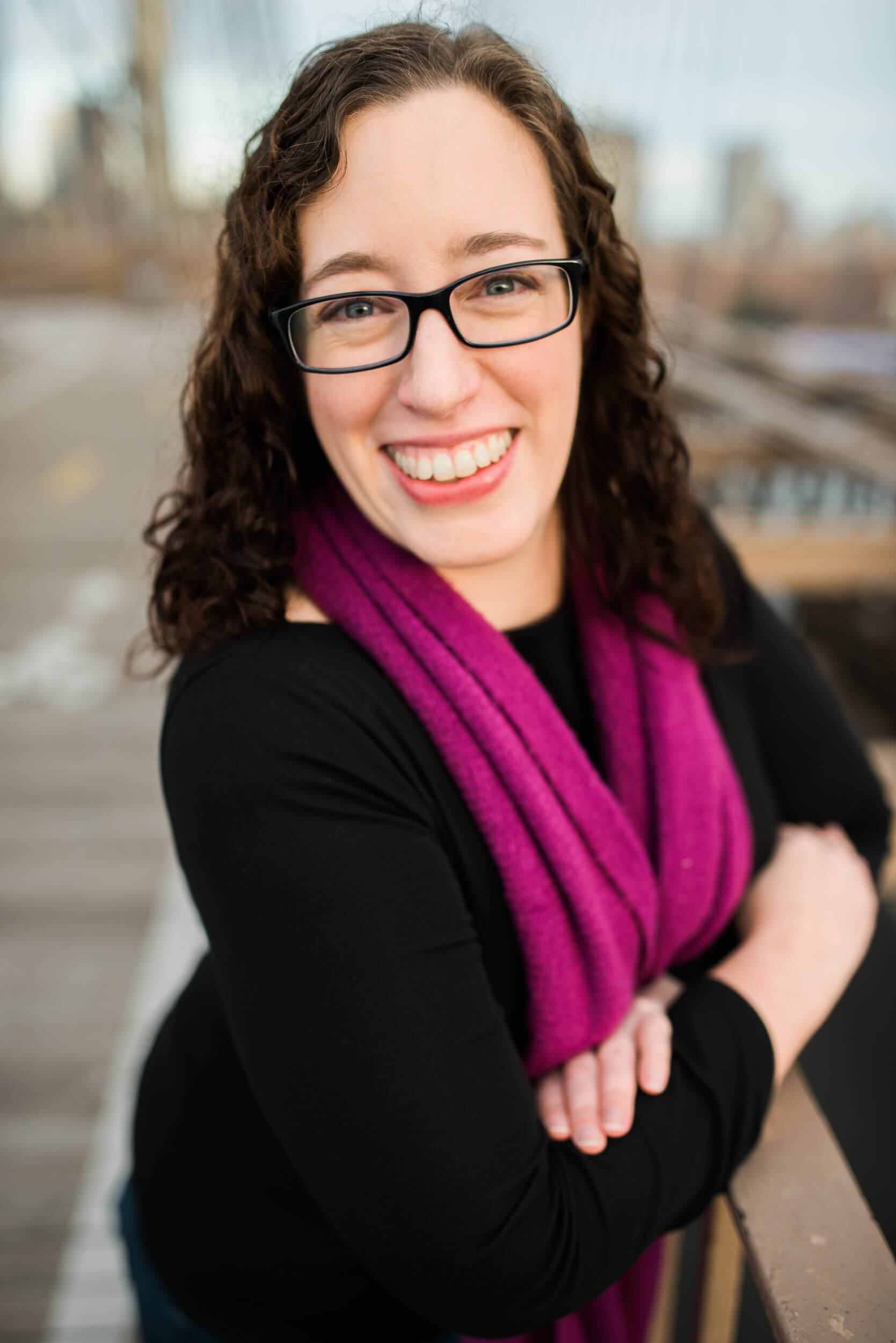 Kathleen Smith Tessitura database specialist at the Intrepid Museum in NY headshot on Brooklyn Bridge at sunrise by Lindsey Victoria Photography
