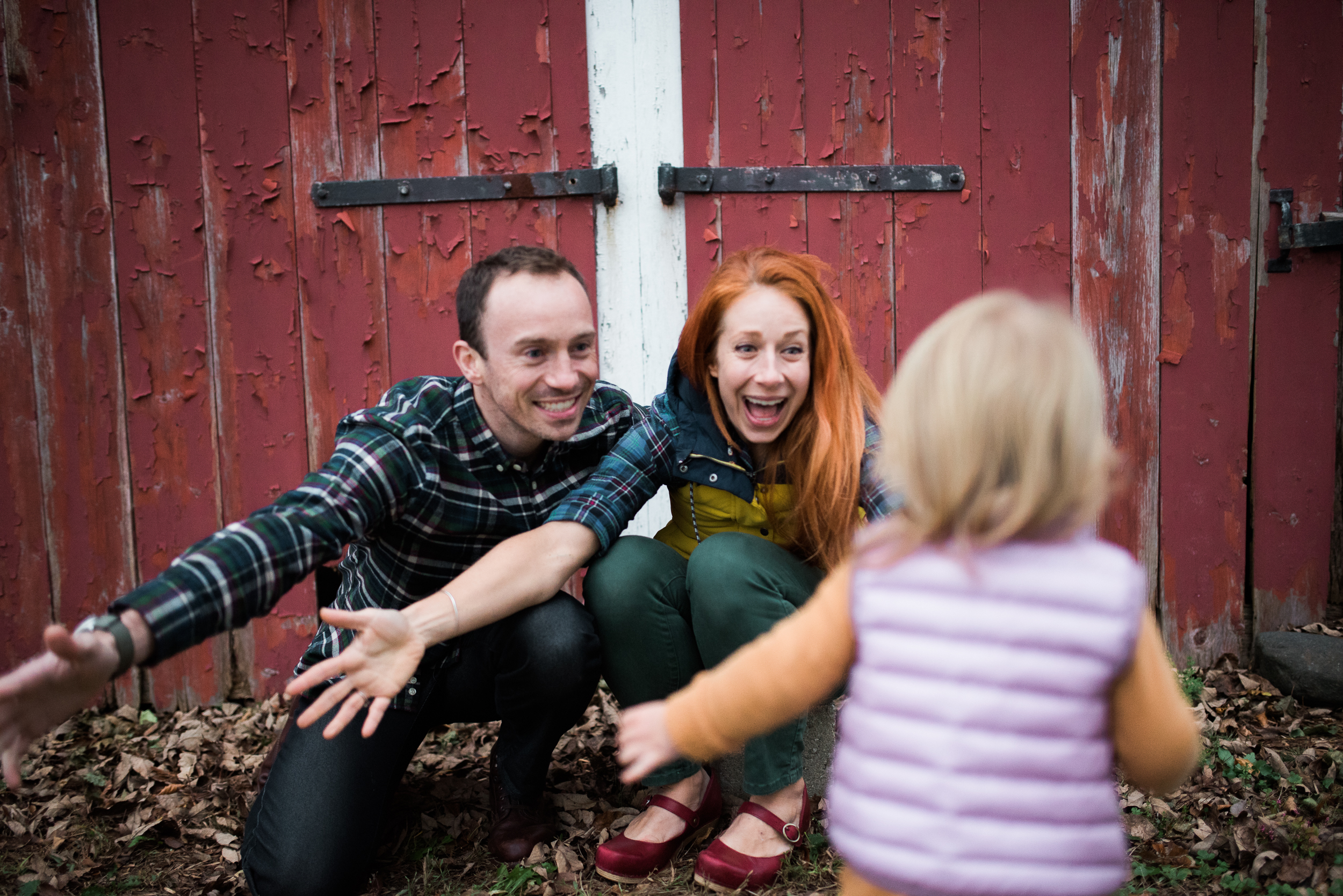 lifestyle family photo playing fun not posed running for a hug red New England barn in Litchfield County Connecticut by Lindsey Victoria Photography