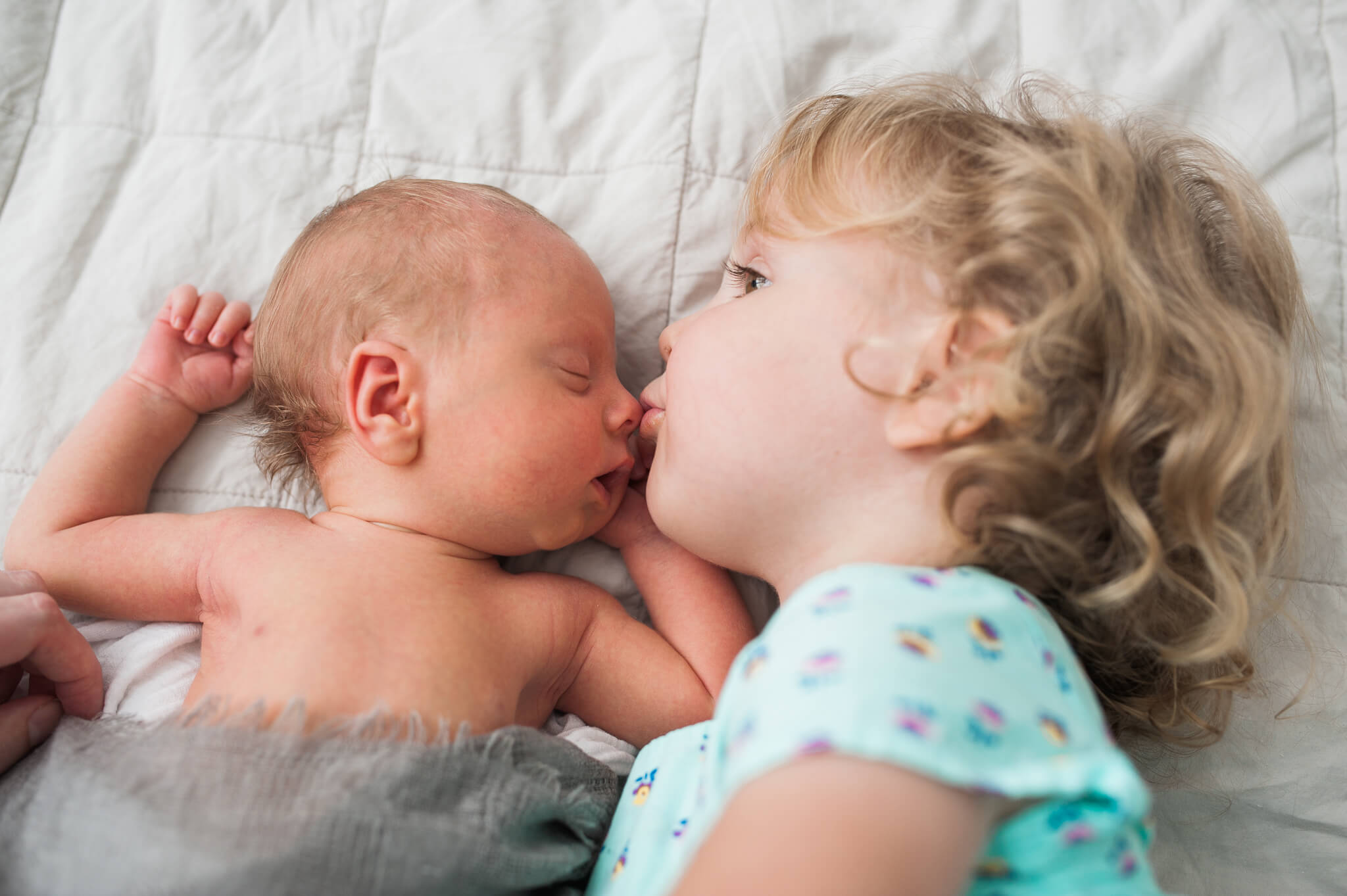 siblings big sister kisses newborn baby brother at home lying on the bed for family photo session in their NYC co-op apartment photo by Lindsey Victoria Photography