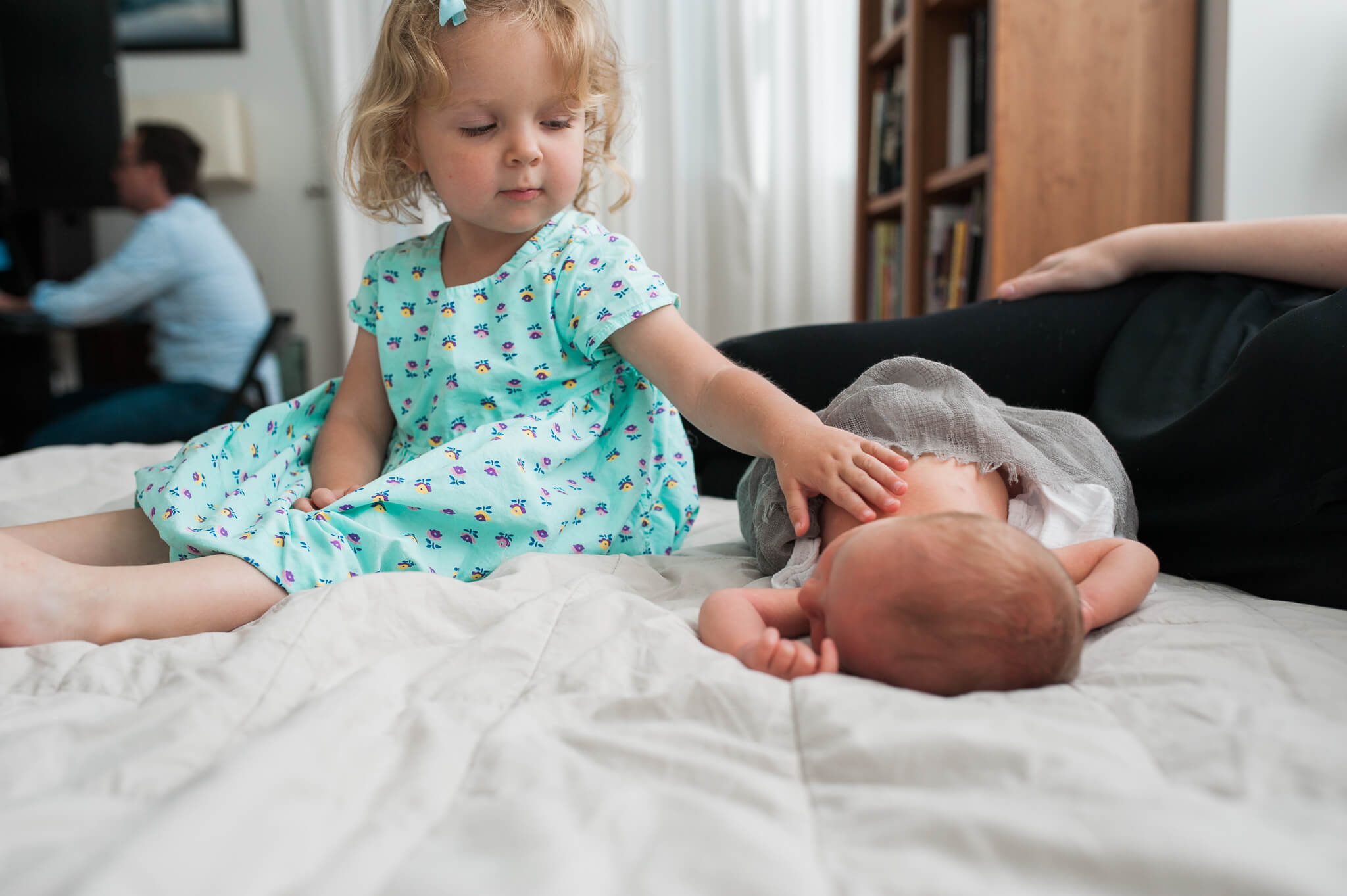 big sister gently touches newborn baby brother during family photo session in their NYC co-op apartment photo by Lindsey Victoria Photography