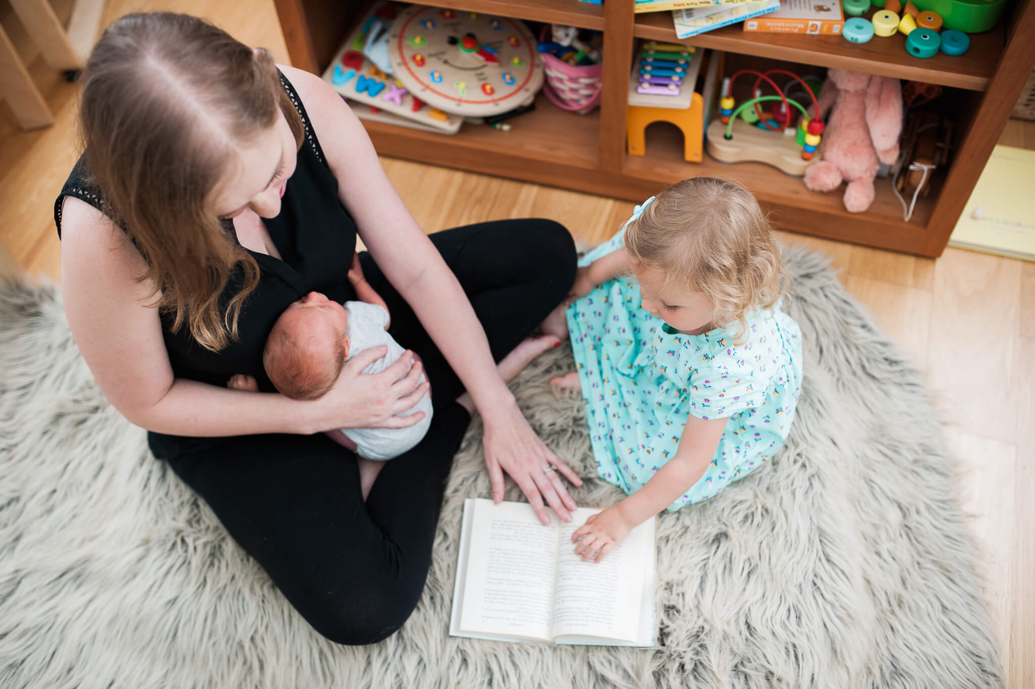 Mother reading to her toddler with newborn in her lap during in-home photo session with Lindsey Victoria Photography in their NYC co-op apartment