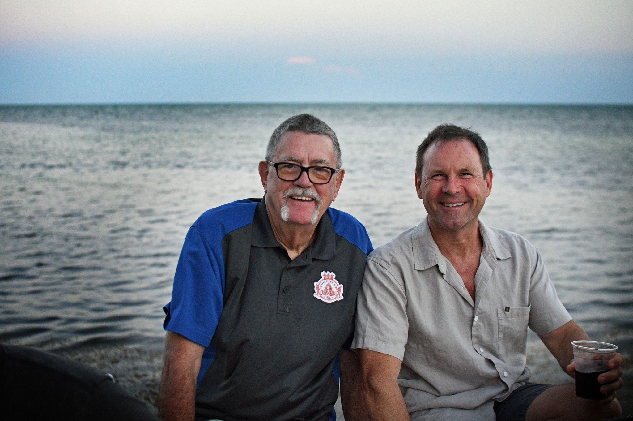 Larry Johnson & Todd German sitting by the ocean