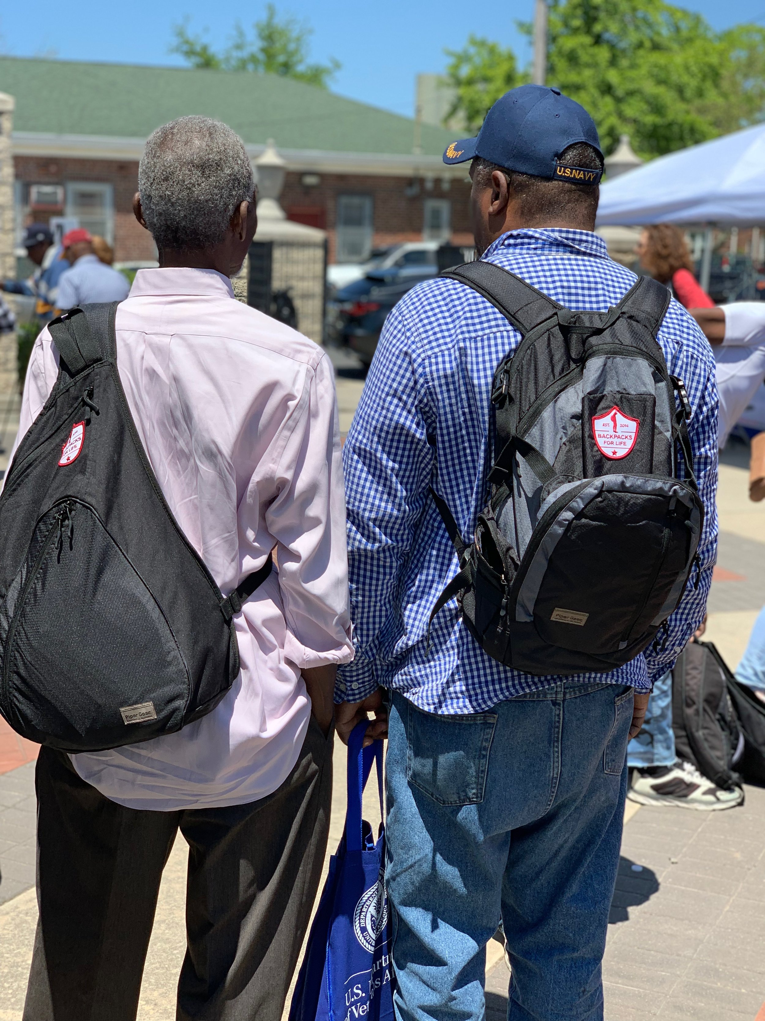 Two veterans showing off their new backpacks