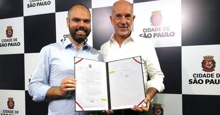 Prefeito Bruno Covas e vereador Xexeu Tripoli (PV) com o PL sancionado (25/6)