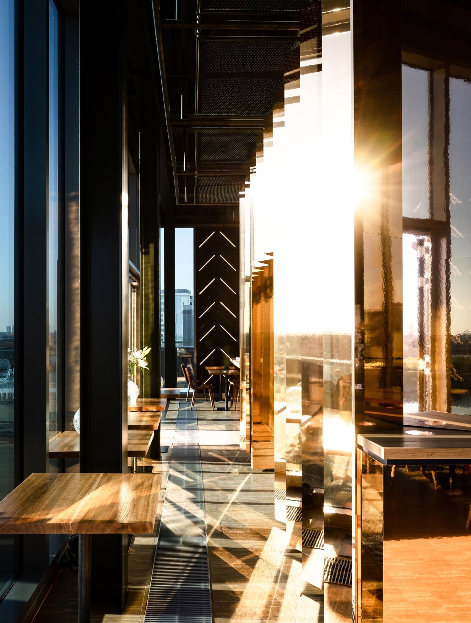 Die Barverkleidung aus hochglänzendem Kupfer im Abendlicht Foto: whitekitchen GbR