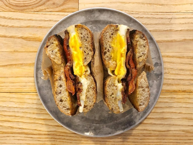 """Bagelsaurus's """"Classic Jumbo"""" comes with egg, cheddar, and mustard butter, but you can add decadent extras, like sun-dried tomatoes, avocado, or bacon for a real breakfast treat.    Courtesy of Bagelsaurus"""