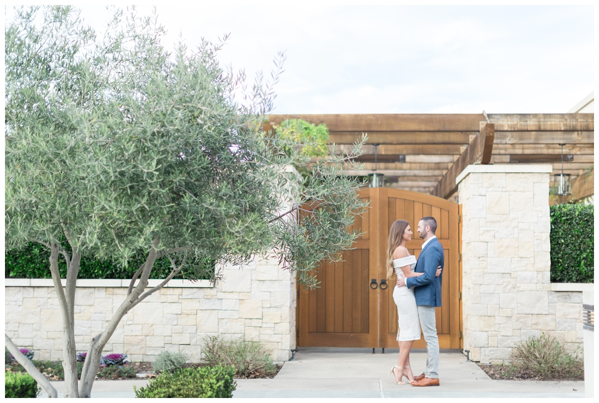 engaged couple dances together while they have engagement photos taken around Sonoma State University