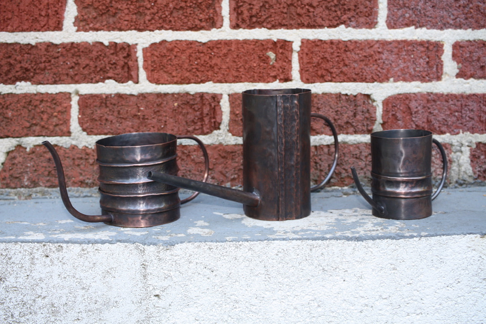 The suite of three (3) copper, fold formed watering cans.